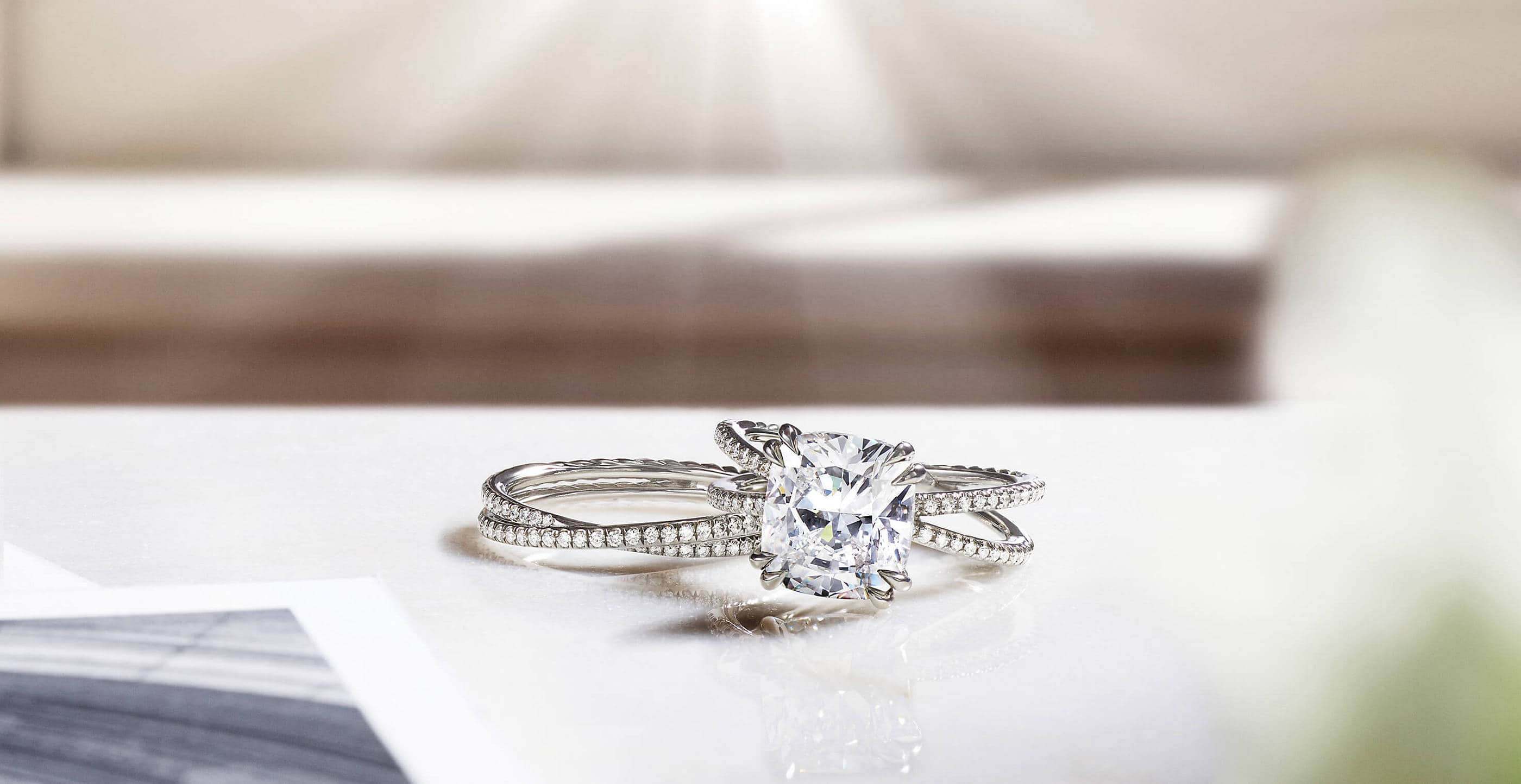 A color photo shows a David Yurman women's Crossover engagement ring atop a matching band ring on a white table near scattered black-and-white photographs. The jewelry is crafted from platinum with diamonds. Behind the rings is a white windowsill with hard shadows.