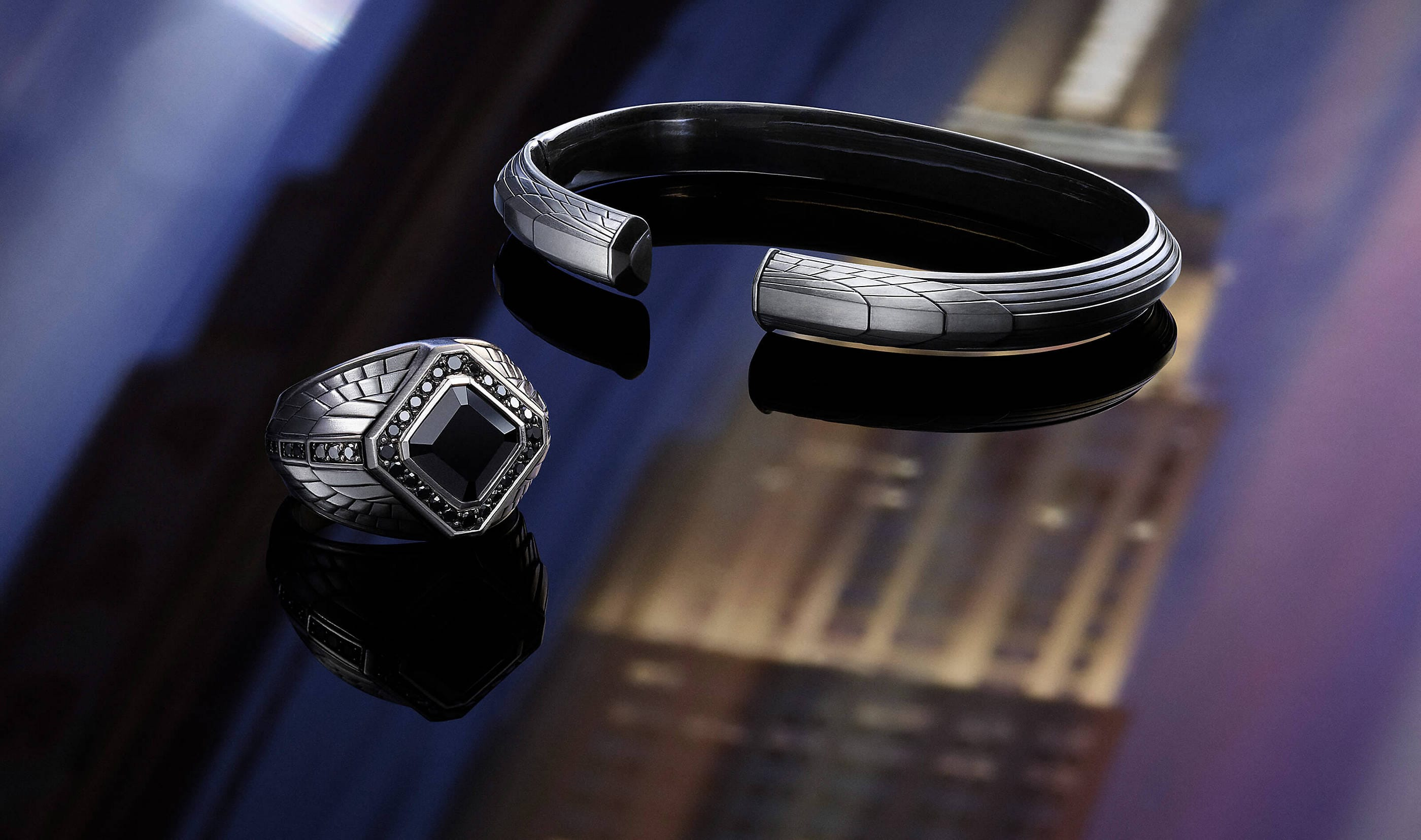 A David Yurman men's signet ring and cuff from the Empire Collection atop a dark surface with reflections of the Empire State Building. The jewelry is crafted from sterling silver with or without black onyx.