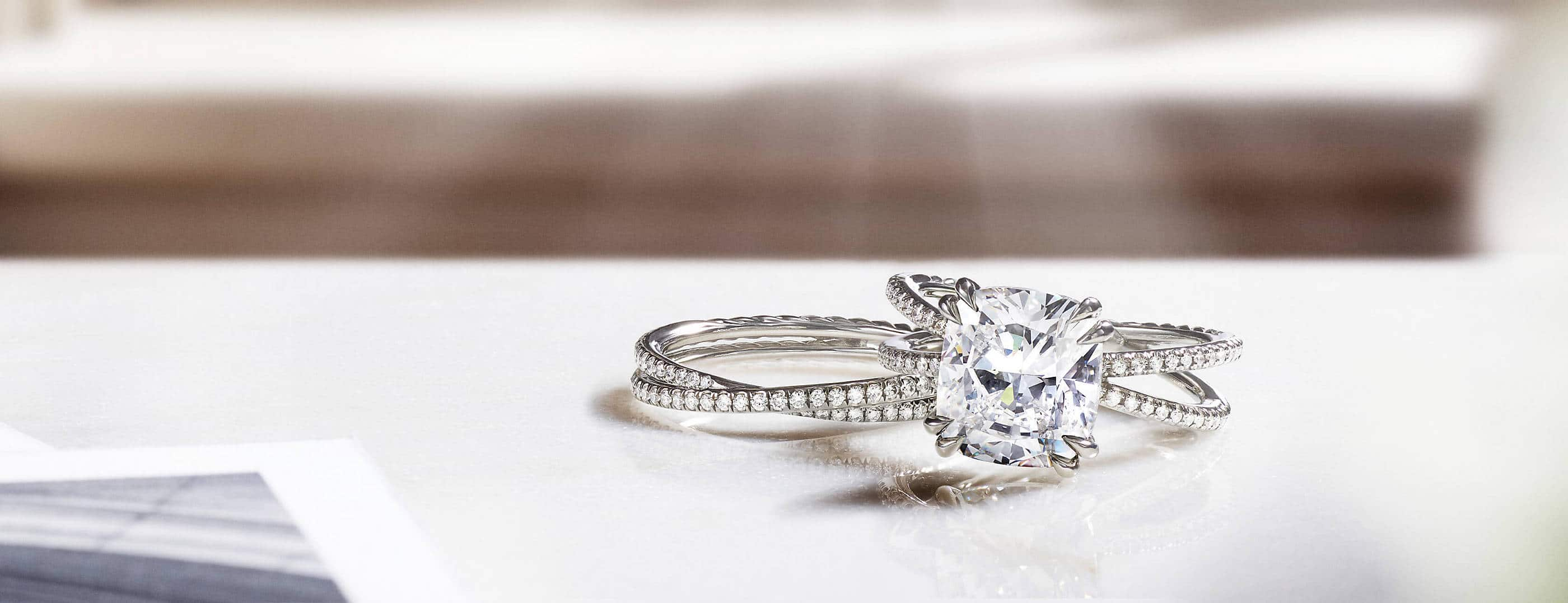 A color photo shows a David Yurman women's Crossover engagement ring atop a matching band ring on a white table near scattered black-and-white photographs. The jewelry is crafted from platinum with diamonds. Behind the rings is a white windowsill with hard shadows