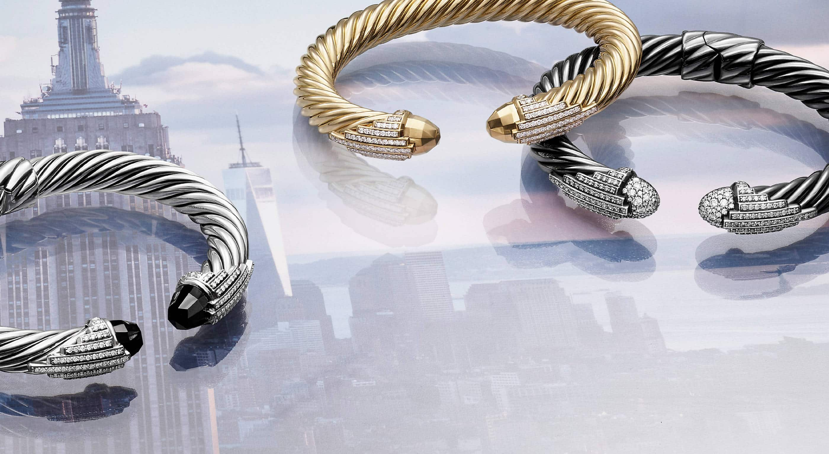 Three David Yurman Empire Collection Cable bracelets over a soft-focus photo of the top of the Empire State Building. The jewelry is crafted from sterling silver with or without black onyx or pavé diamond end caps.
