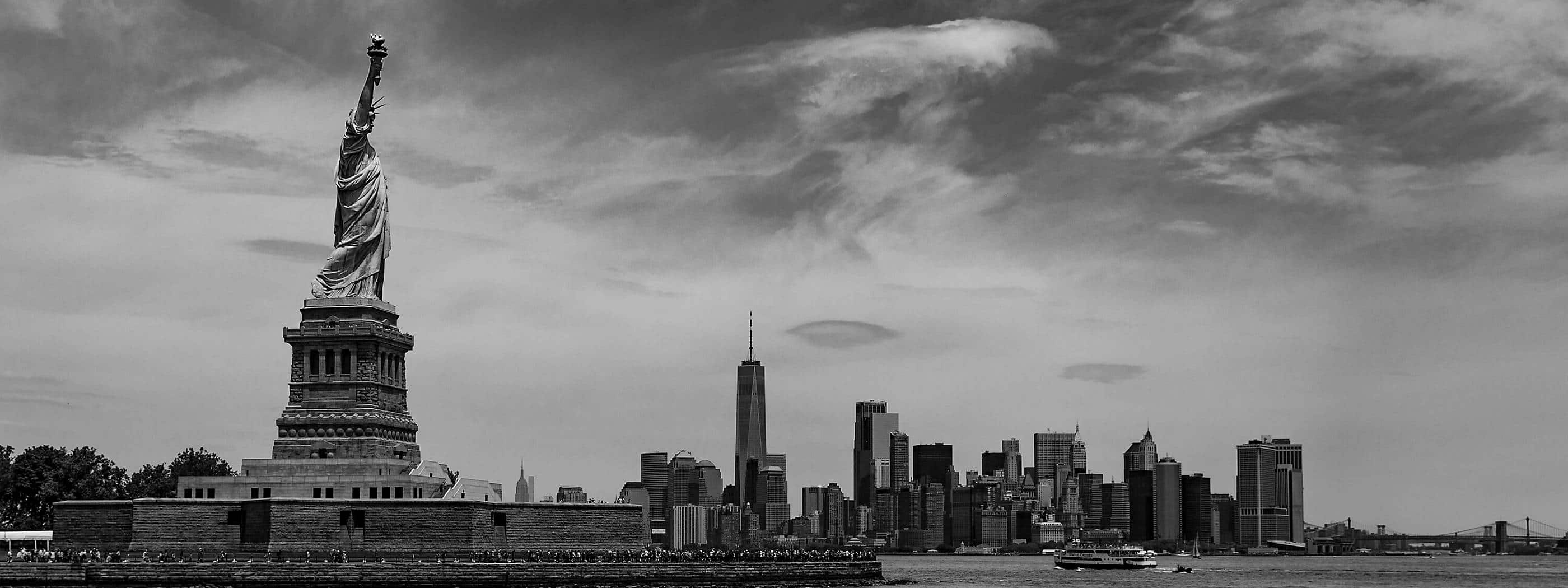 A black-and-white photo shows the Statue of Liberty to the left of the Manhattan skyline.