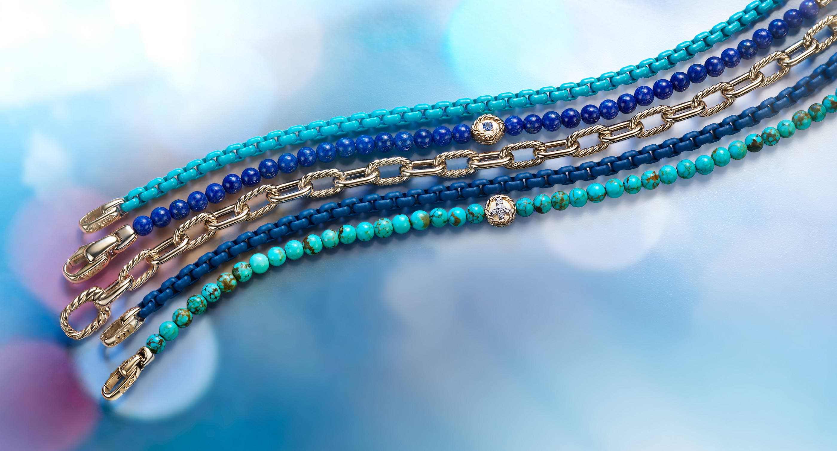 An image of four David Yurman women's blue, gold and turquoise-hued chain and beaded bracelets lined up in a vertical stack atop a blue background with colorful reflections of light. The jewelry is crafted from 18K yellow gold with or without acrylic-coated stainless steel, lapis lazuli beads, turquoise beads, pavé diamonds and blue sapphires.