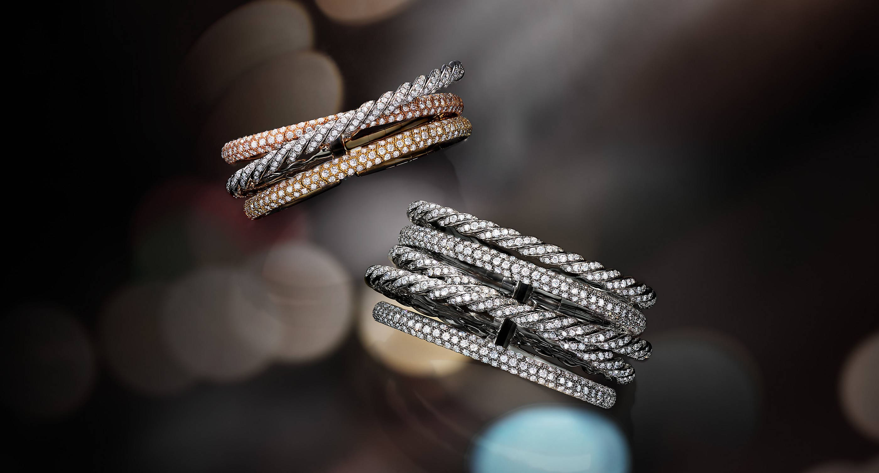 An image of two David Yurman Pavéflex multi-row cuff bracelets suspended in front of a black-and-grey surface with colorful reflections of light. One bracelet is crafted from all 18K white gold with pavé diamonds while the other is crafted from 18K yellow, white and rose gold with pavé diamonds..