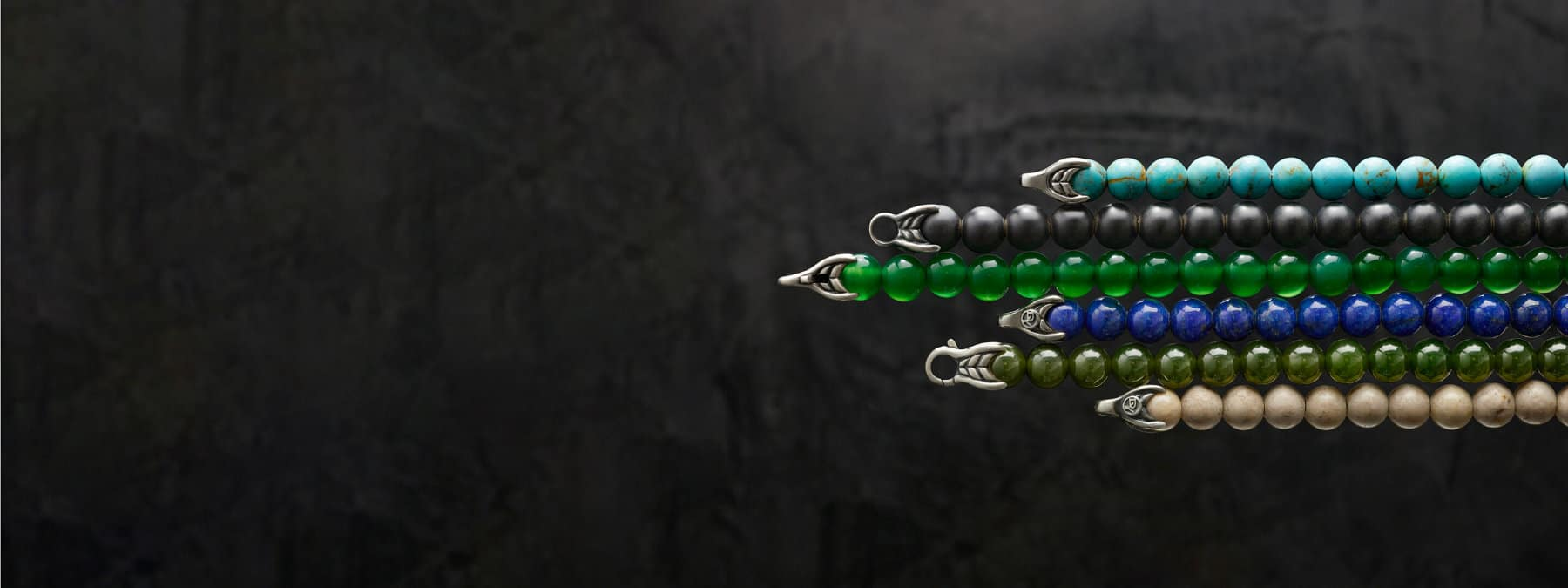 A color photo shows six David Yurman Spiritual Beads bracelets placed atop a black background. The jewelry is crafted from various colored gemstones and sterling silver.