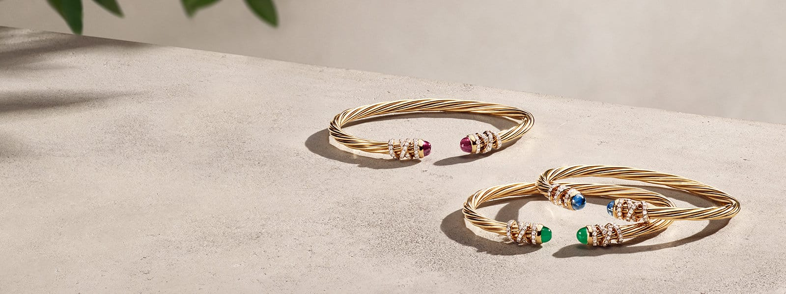 Three David Yurman Helena bracelets in 18K yellow gold with pavé diamond threads and colored gemstone end caps—all scattered on a light pink stone background with shadows in one corner.