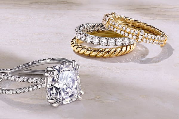 A color photo shows a David Yurman women's Crossover engagement ring and two stacks of women's wedding bands scattered on a beige marble surface with soft diagonal shadows. The jewelry is crafted from platinum, 18K yellow or white gold with or without white diamonds.