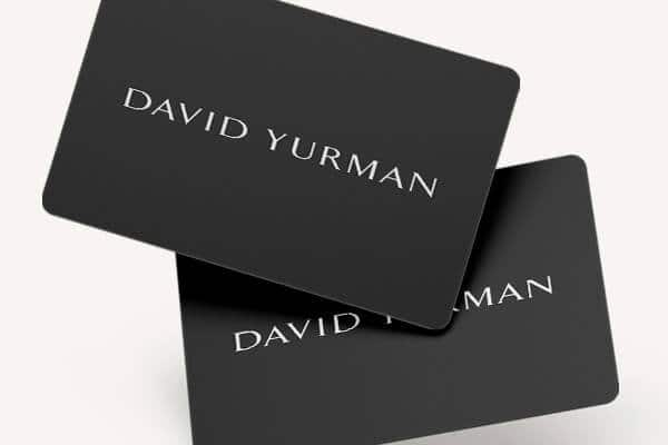 A color photograph shows a black David Yurman gift card, with the David Yurman logo written in white across the center front, standing upright on a white surface and casing a long shadow.
