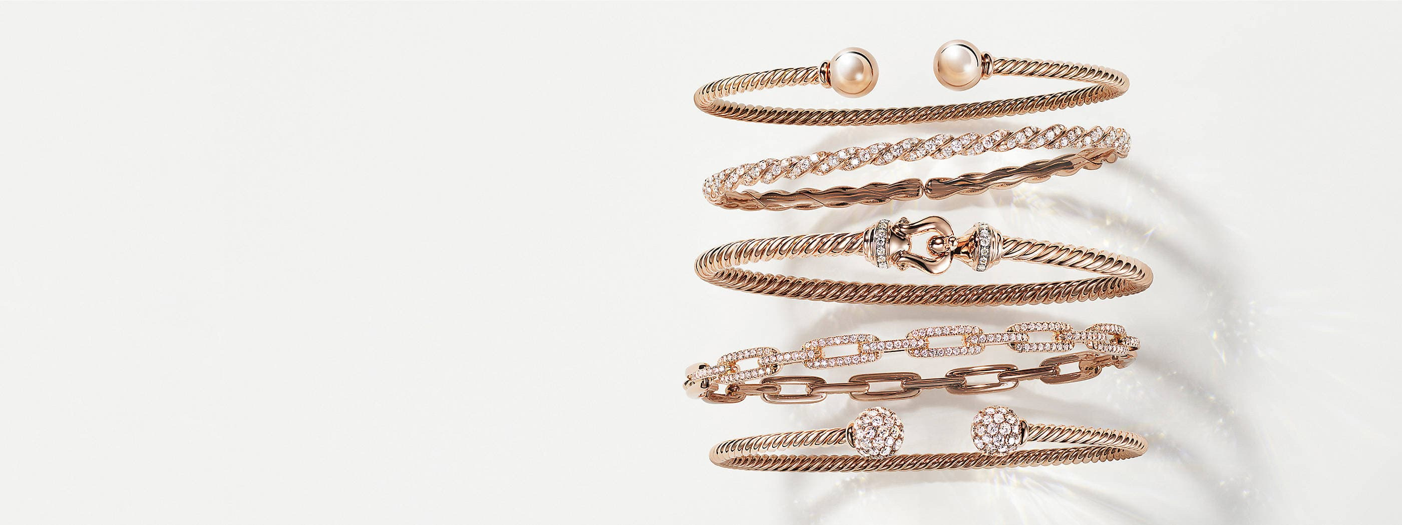 A color photograph shows a vertical row of five David Yurman bracelets on a white background. The women's jewelry is crafted from 18K yellow gold with pavé diamonds. Four of the bracelets feature Cable, a buckle motif or ball-shaped ends, while one bracelet is a chain-link design