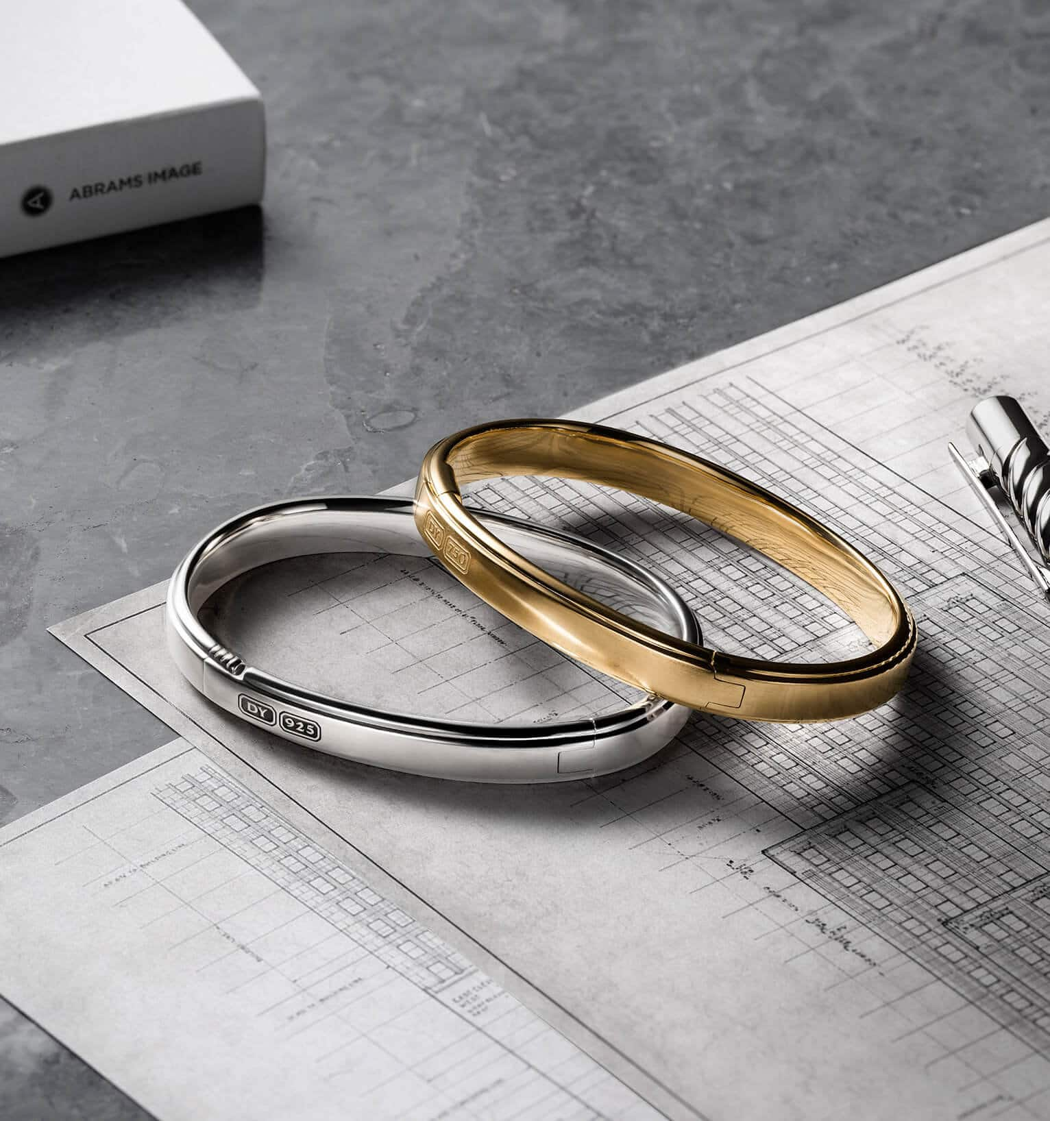 A color photo shows two David Yurman men's cuff bracelets atop architectural blueprints scattered on a grey marble surface. One bracelet is crafted from sterling silver while the other is crafted from 18K yellow gold. A grey book and a sterling silver David Yurman Cable pen surround the bracelets.