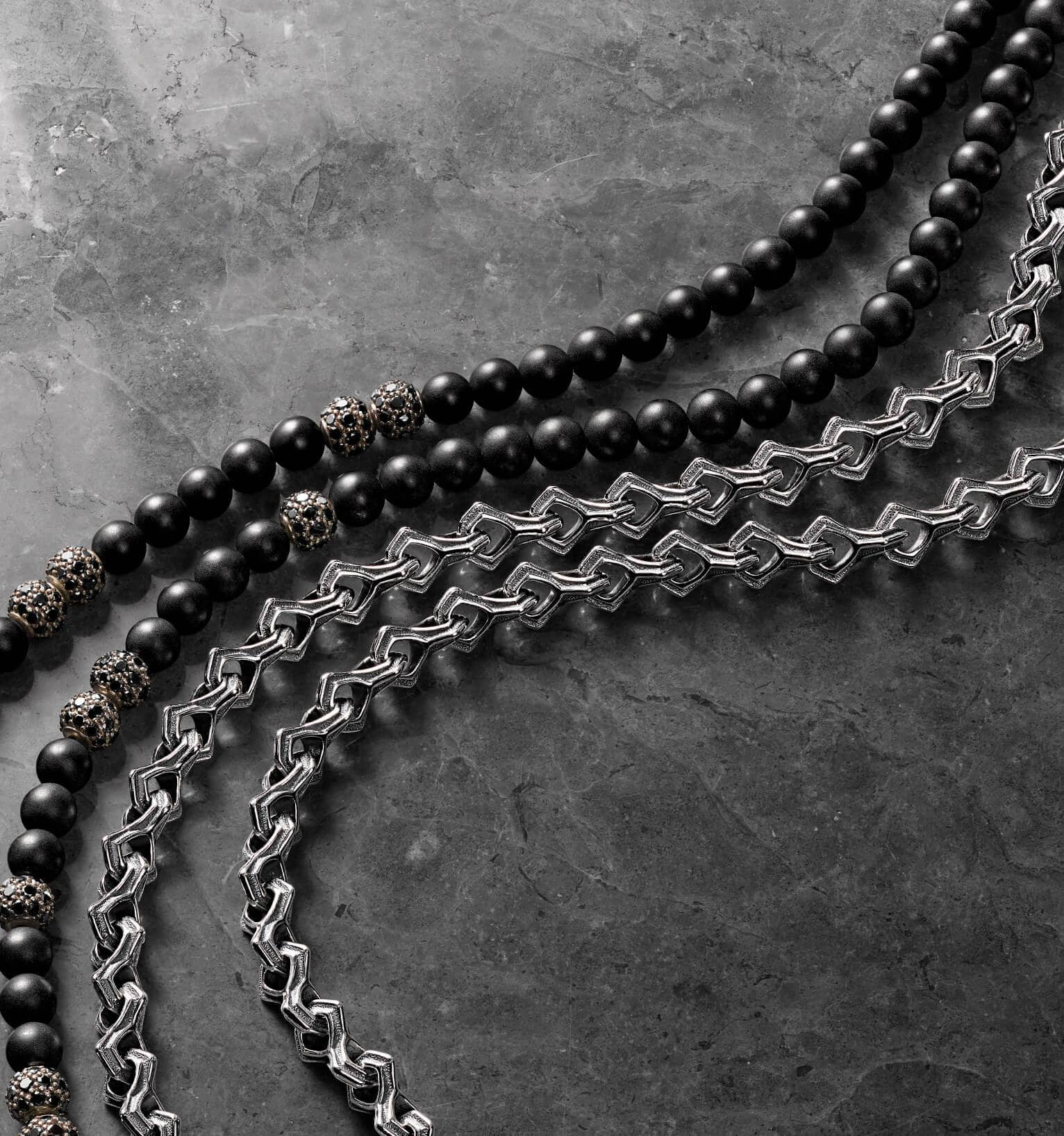 A color photograph shows four David Yurman men's necklaces from the Spiritual Beads and Armory collections arranged in a row atop a grey marble surface. Two chain necklaces are crafted from sterling silver, two necklaces are crafted from sterling silver with black onyx beads and black diamond accents.