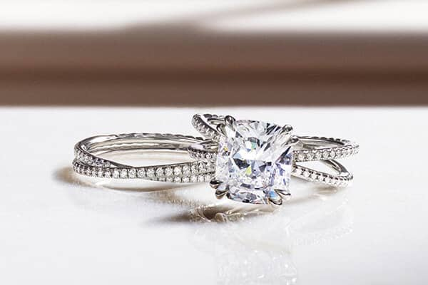 A color photo shows a David Yurman women's Crossover engagement ring atop a matching band ring on a white table. The jewelry is crafted from platinum with diamonds. Behind the rings is a white windowsill with hard shadows
