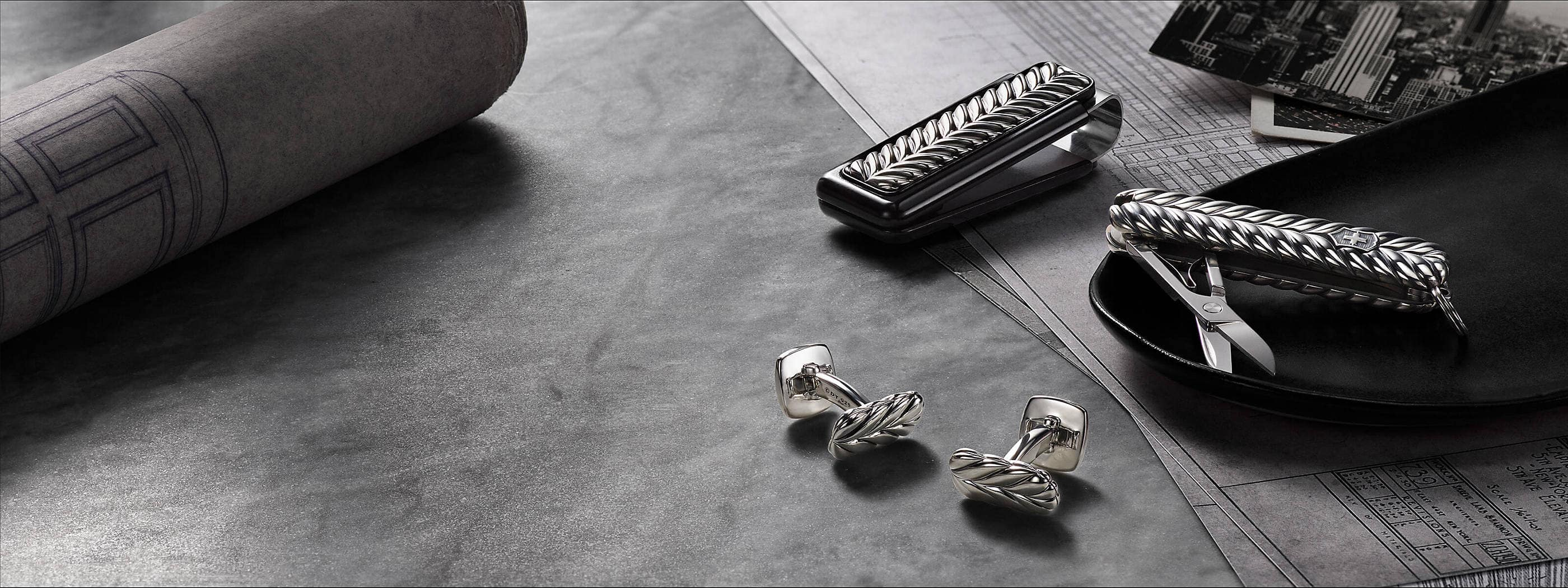 A color photo shows a pair of David Yurman men's cufflinks scattered on a grey marble surface next to a black tray holding a Swiss Army knife with the scissors shown and a money clip atop architectural blueprints. The accessories are crafted from sterling silver and are part of the Chevron Collection. On the left is a rolled up architectural blueprint and on the very right is a black-and-white photograph of a skyscraper.