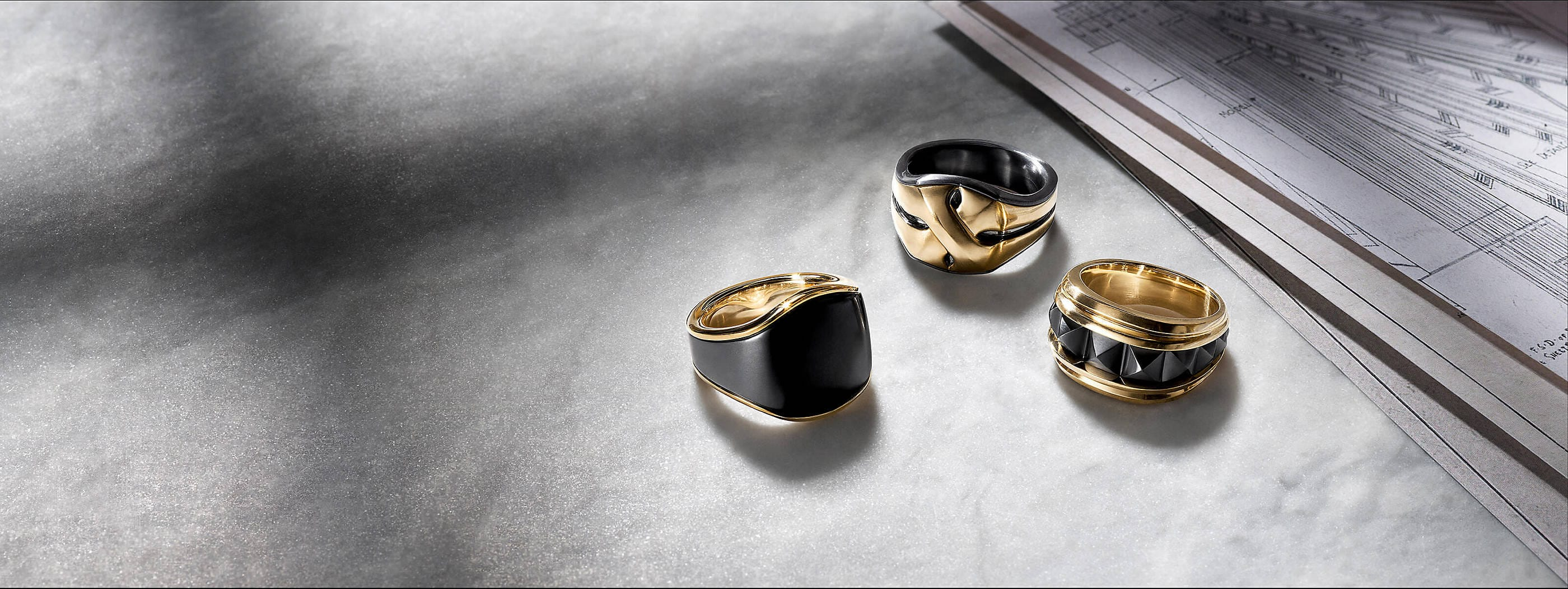 A  color photo shows three David Yurman men's rings from the Streamline, Armory and Pyramid collections on a grey marble surface next to architectural blueprints. The jewelry is crafted from 18K yellow gold with black titanium.
