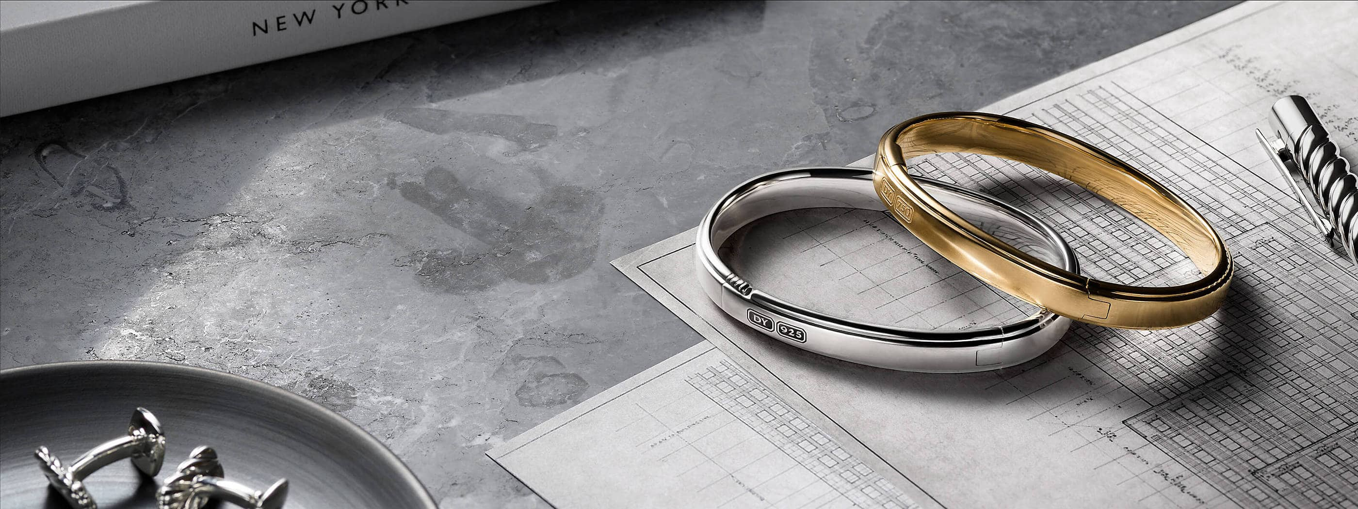 A color photo shows two David Yurman men's cuff bracelets atop architectural blueprints scattered on a grey marble surface. One bracelet is crafted from sterling silver while the other is crafted from 18K yellow gold. A grey book about New York, a sterling silver David Yurman Cable pen and a pair of David Yurman sterling silver cufflinks on a grey dish surround the bracelets.