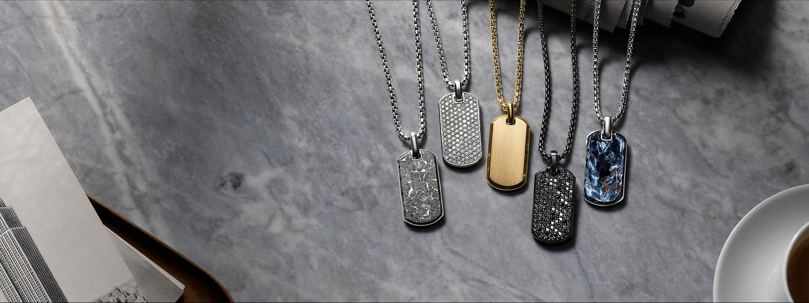 A color photograph shows five David Yurman men's tags strung on sterling silver, 18K yellow gold or black titanium box chains placed in a row on a grey marble surface. Three of the tags are crafted from sterling silver with pietersite, white diamonds or meteorite. One tag is crafted from 18K yellow gold. The final tag is crafted from black titanium with black diamonds. To the right of the jewelry is a white cup and saucer; to the left is a black-and-white photo of a skyscraper on a metal tray.