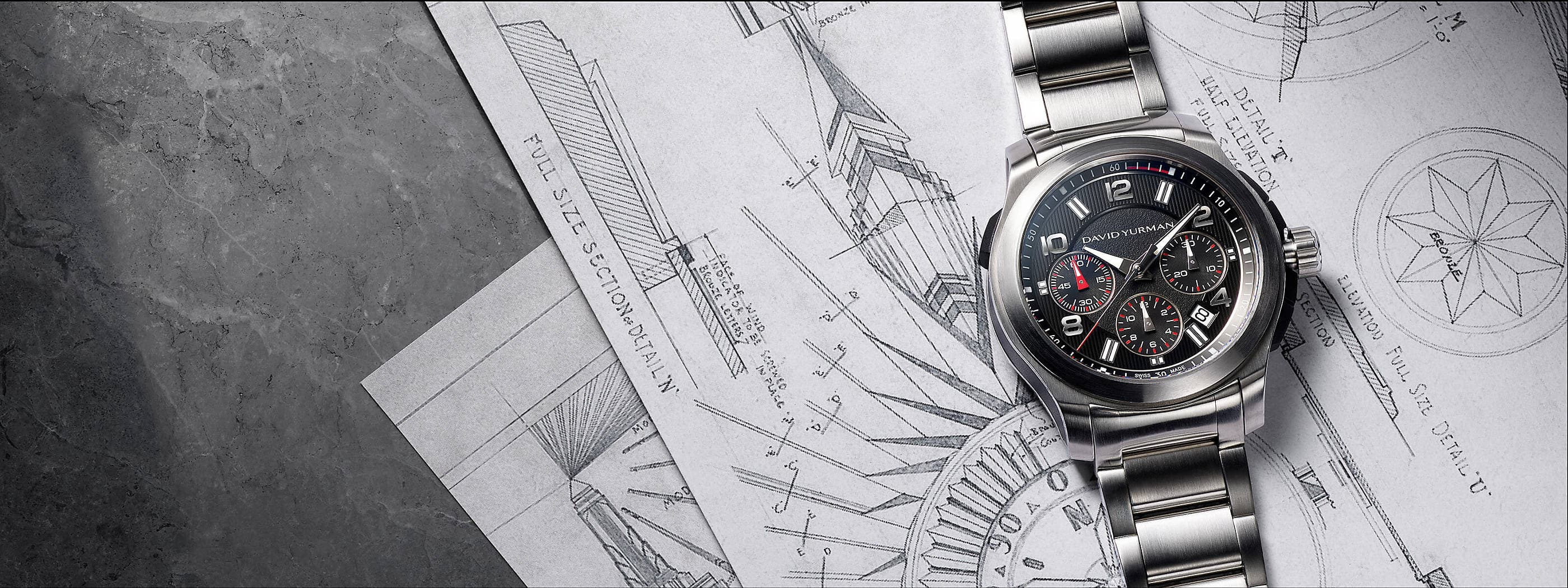 A color photograph shows a David Yurman men's Revolution chronograph placed atop architectural blueprints on a grey marble surface. The watch is crafted with a stainless-steel case and a black-and-silver dial.