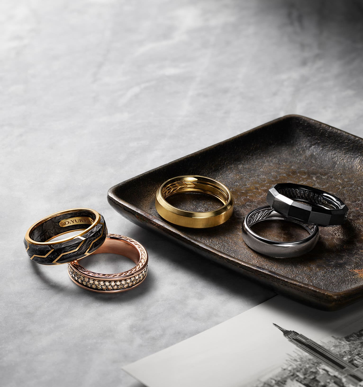 A color photo shows two David Yurman men's band rings scattered on a grey marble surface next to a scratched, rusted metal dish holding three David Yurman men's band rings. The jewelry is crafted from 18K yellow gold with or without forged carbon, 18K rose gold with cognac diamonds, 18K white gold or black titanium.