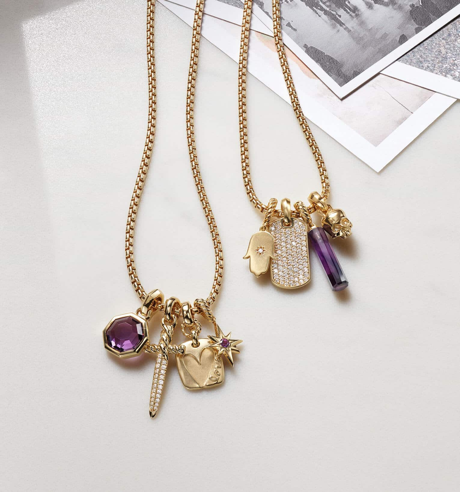 A color photograph shows two David Yurman chain necklaces strung with four amulet pendants each. The women's jewelry is crafted from 18K yellow gold with or without pavé diamonds and amethyst. The pendants come in various shapes such as a tag, octagon, dagger, star, hamsa hand or skull. The jewelry is lying on a white background with dark shadows near three black-and-white photographs