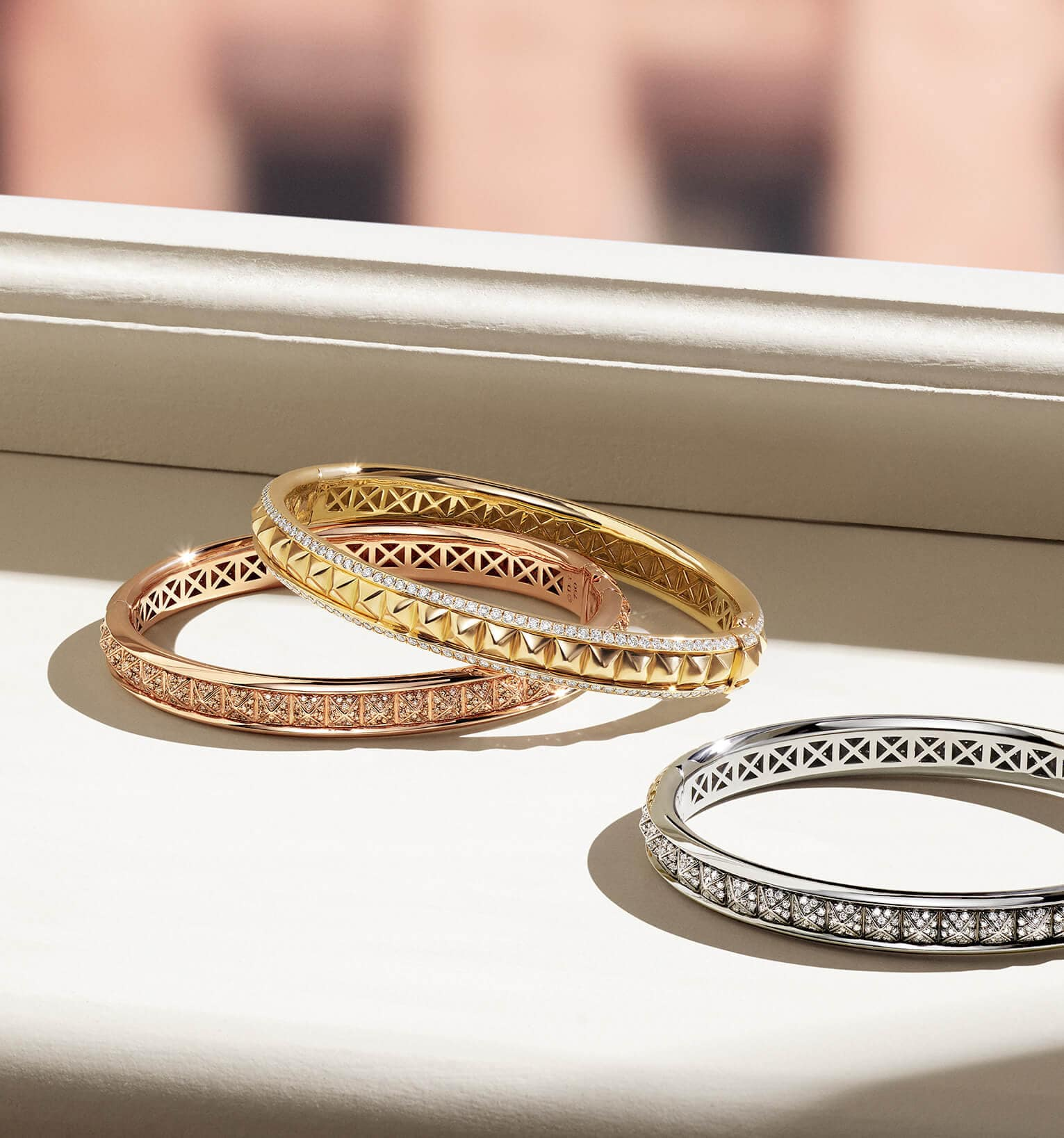 A color photo shows three David Yurman women's bracelets from the Modern Renaissance collection scattered on a white windowsill with a view of a brick building. The jewelry is crafted from 18K rose or yellow gold with cognac or white diamond accents. One bracelet is crafted from 18 white gold with white diamond accents.