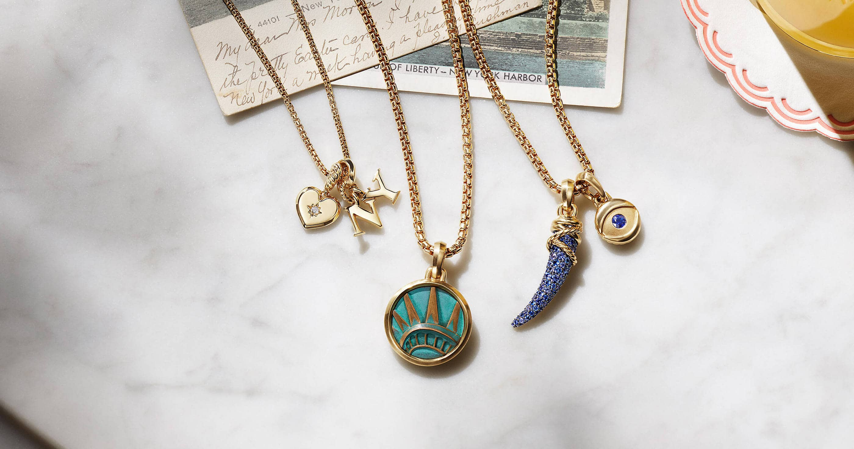 "A color photo shows three David Yurman chain necklaces strung with amulet pendants, all lying on a marble table next to two New York postcards. The women's jewelry is crafted from 18K yellow gold with or without pavé diamonds and sapphires. The pendants come in various shapes such as a heart, dagger, evil eye or ""NY"" initials. One pendant depicts the crown of the Statue of Liberty."