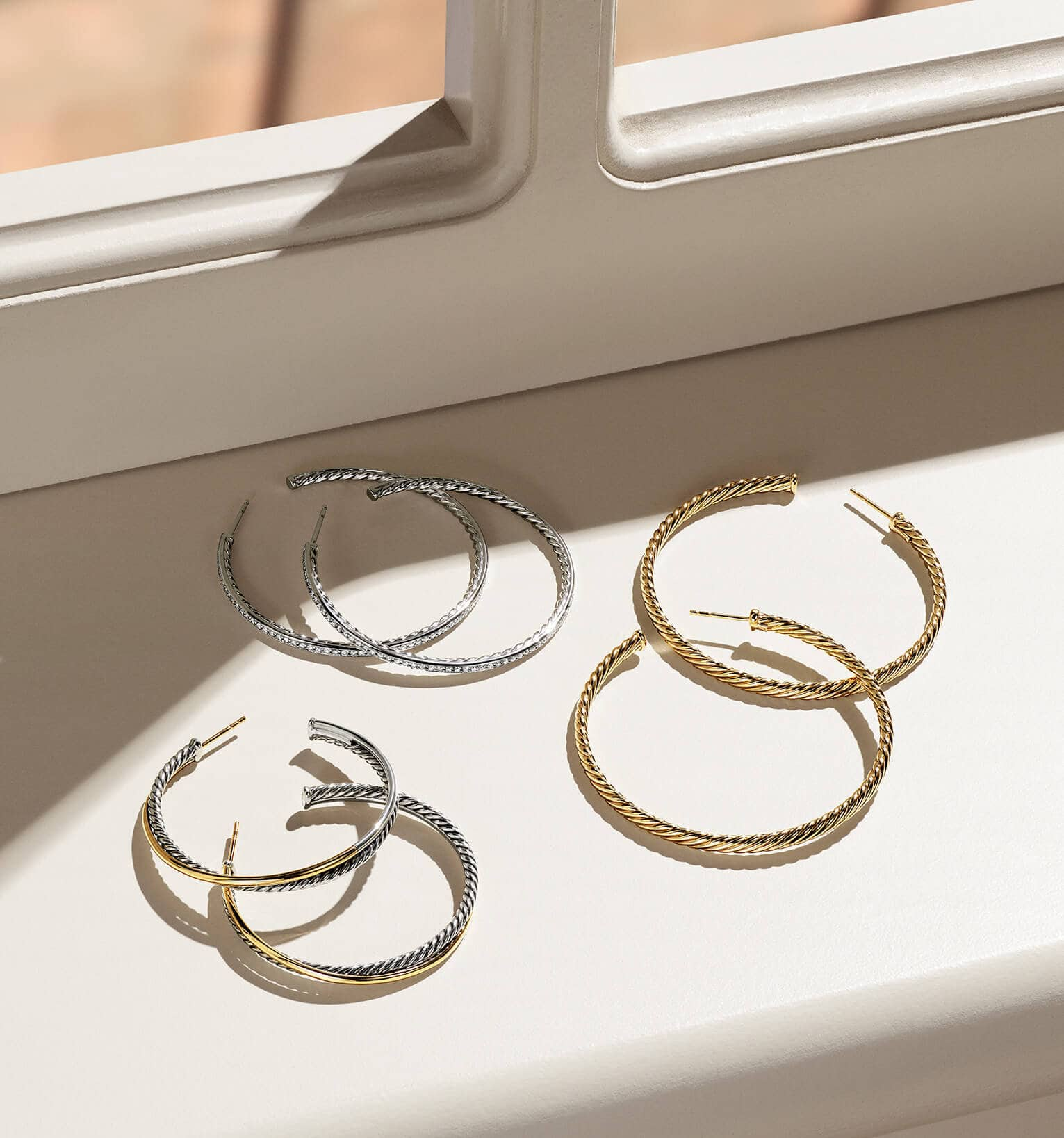 A color photograph shows three pairs of David Yurman women's hoop earrings from the Cable Collection scattered on a white windowsill with hard shadows. The jewelry is crafted from Cabled 18K yellow gold or sterling silver with or without 18K yellow gold accents.