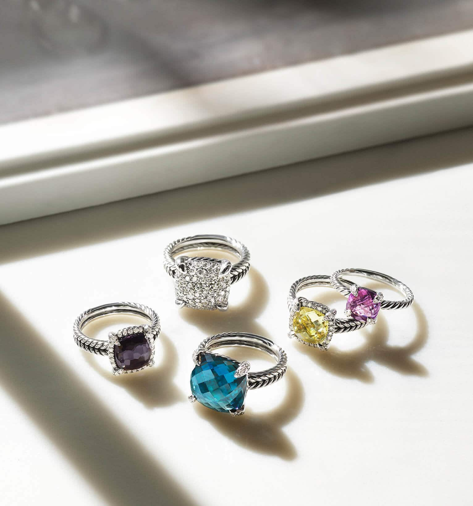 A color photograph shows five David Yurman women's rings from the Châtelaine Collection scattered on a white windowsill with hard shadows and white flowers. The jewelry is crafted from sterling silver with pavé diamonds and with or without a faceted cushion-shaped black orchid, blue topaz, lemon citrine or amethyst center stone.