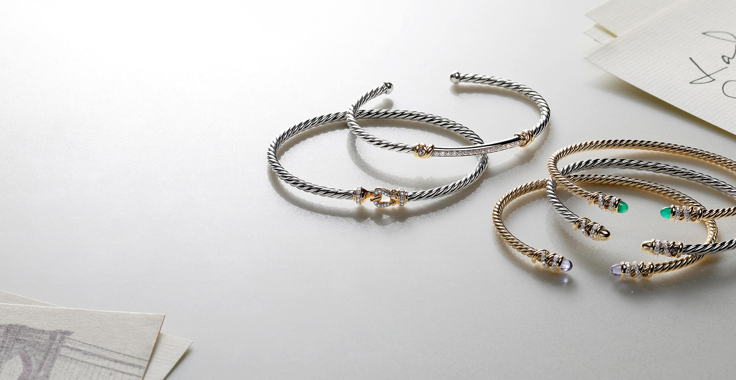 A color photo shows five David Yurman bracelets from the Helena and Buckle collections scattered on a white backdrop next to a stack of white notecards with handwriting and a black-and-white postcard of a bridge. Two of the women's bracelets are crafted from 18K yellow gold with pavé diamond or emerald accents. Three of the women's bracelets are crafted from sterling silver with 18K yellow gold and pavé diamond accents.
