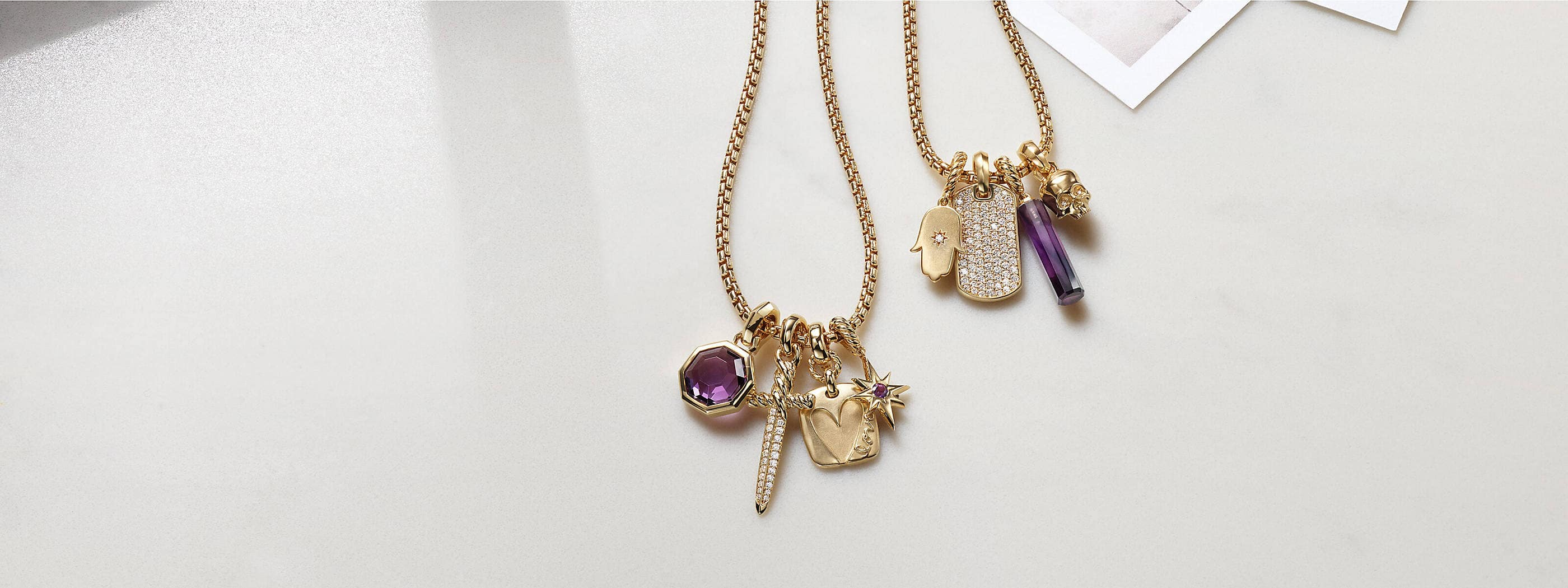 A color photograph shows two David Yurman chain necklaces strung with four amulet pendants each. The women's jewelry is crafted from 18K yellow gold with or without pavé diamonds and amethyst. The pendants come in various shapes such as a tag, octagon, dagger, star, hamsa hand or skull. The jewelry is lying on a white background with dark shadows near three black-and-white photographs.