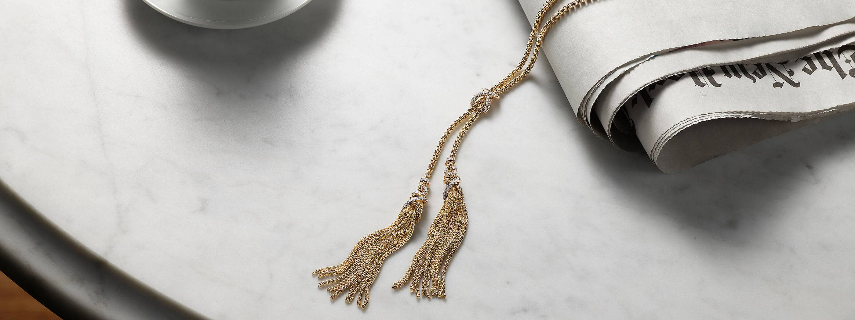 A color photo shows a David Yurman Helena lariat necklace lying on a marble table atop the New York Times and nearby a white saucer. The women's jewelry is crafted from 18K yellow gold with pavé diamond accents near its tasseled ends.