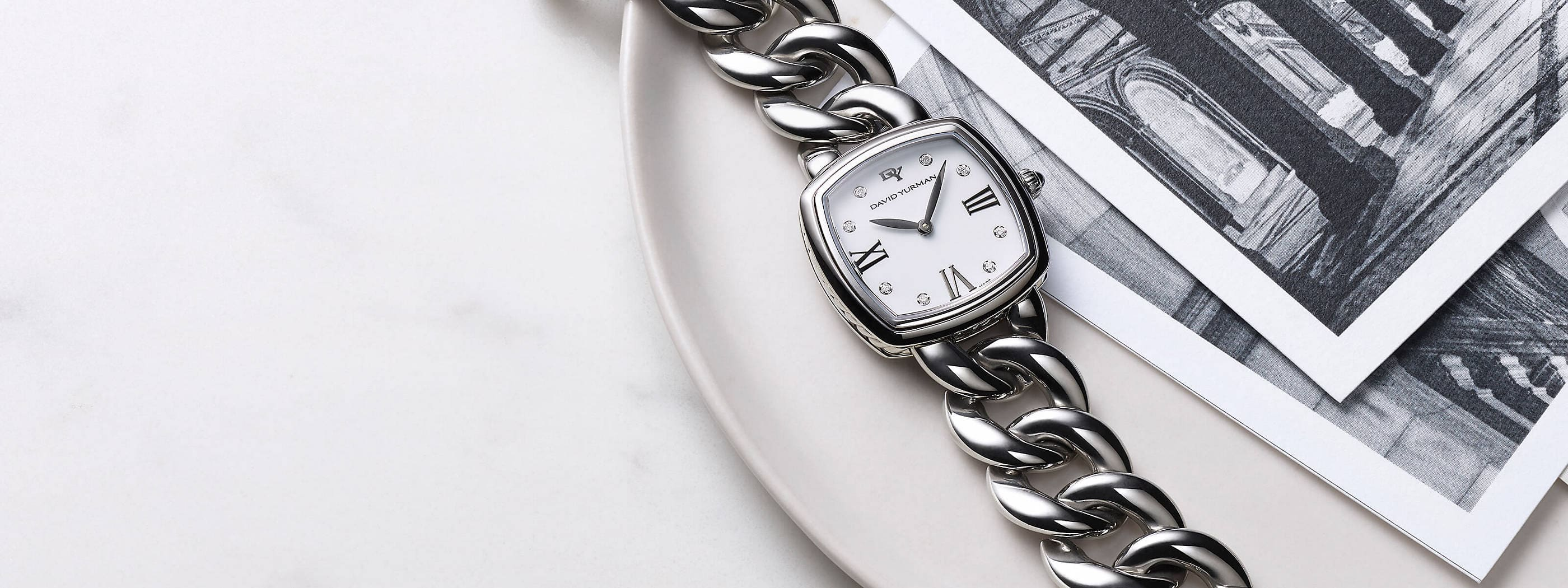 A color photograph shows a marble surface and a David Yurman women's Albion bracelet watch on a beige dish next to black-and-white architectural photographs. The watch is crafted from stainless steel with pavé diamonds.