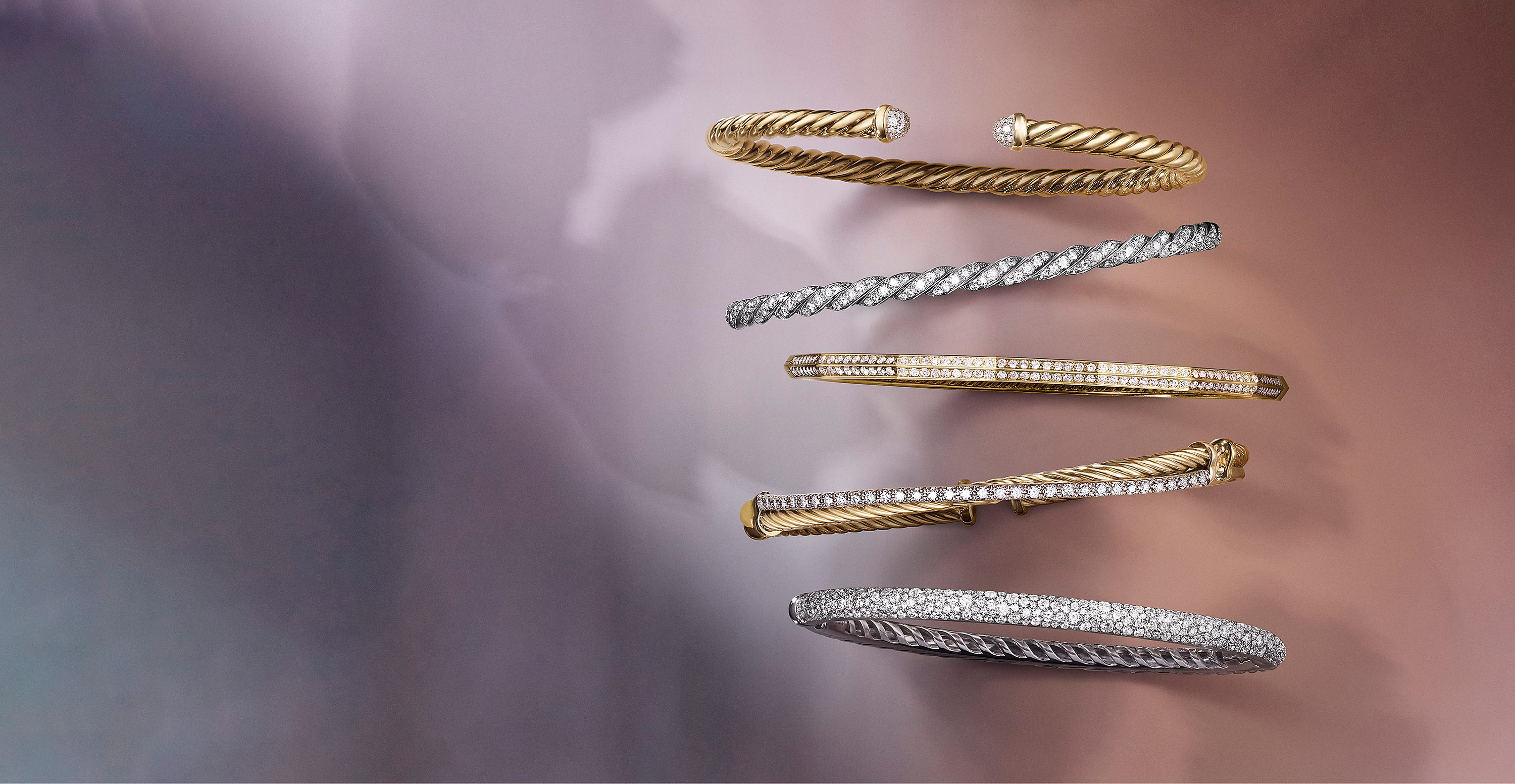 A color photo shows five David Yurman bracelets placed in a vertical stack atop a pink background with soft shadows. Two of the women's bracelets are crafted from 18K white gold with pavé white diamond. The other bracelets are crafted from 18K yellow gold with pavé white diamonds.