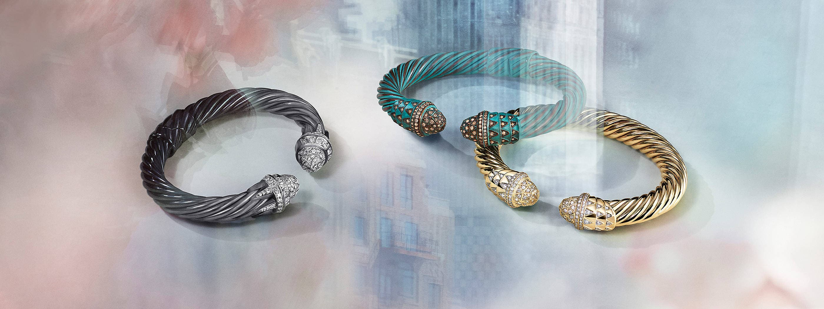 A color photo shows three David Yurman women's Cable bracelets scattered on a white background with soft-focus flowers, city buildings and reflections of light. Two of the bracelets feature Art Deco-inspired motifs in white diamonds at the ends and are crafted from darkened sterling silver or 18K yellow gold. The other bracelet is crafted from green-hued copper with cognac diamonds set in a pattern inspired by the Statue of Liberty.