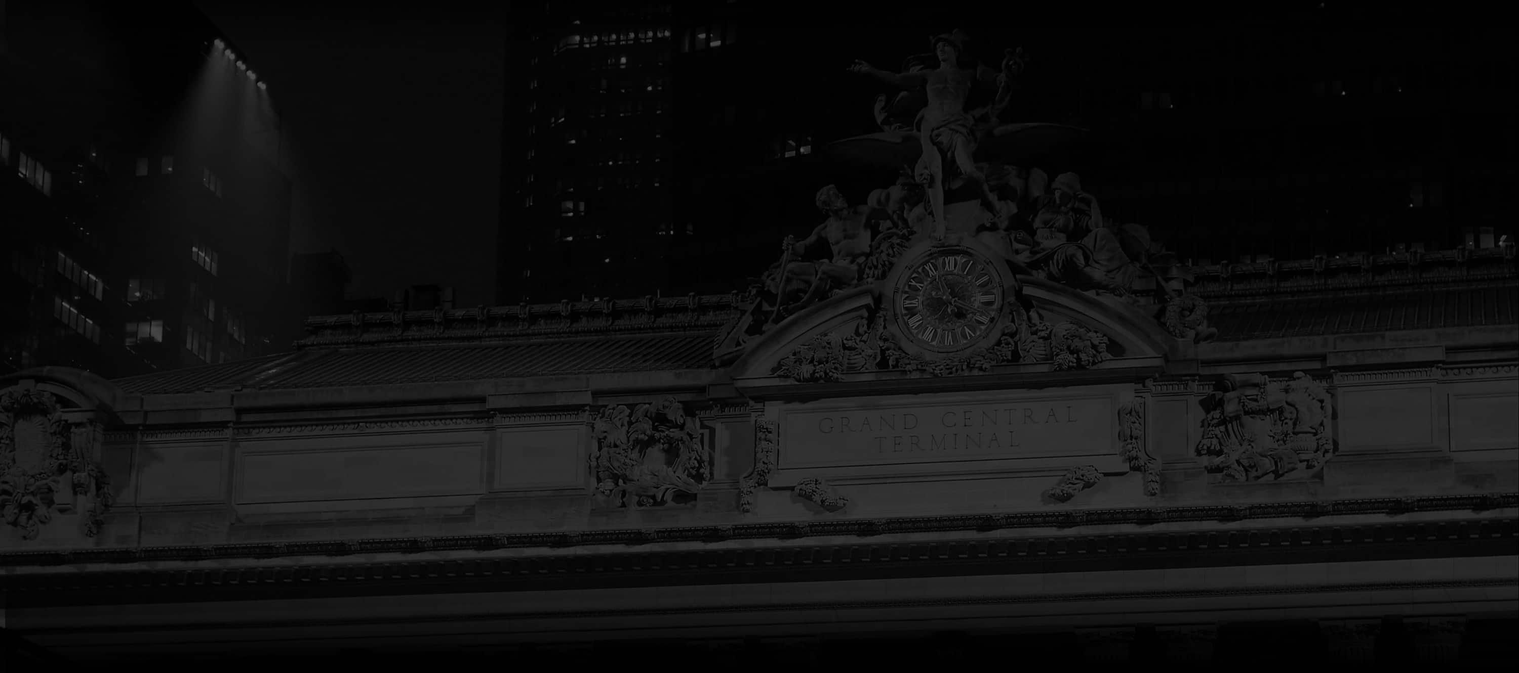 A dark black-and-white photo of the front of Grand Central Station in NYC.