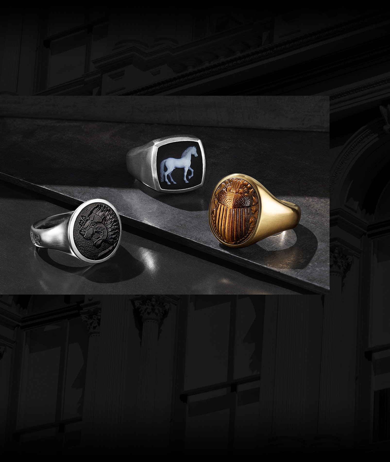 An image of three Petrvs signet rings scattered on a dark grey stepped stone surface. The rings each feature a carved center gemstone with a lion, horse or scarab in black onyx, banded agate or tiger's eye. The jewelry is crafted from sterling silver or 18K yellow gold.
