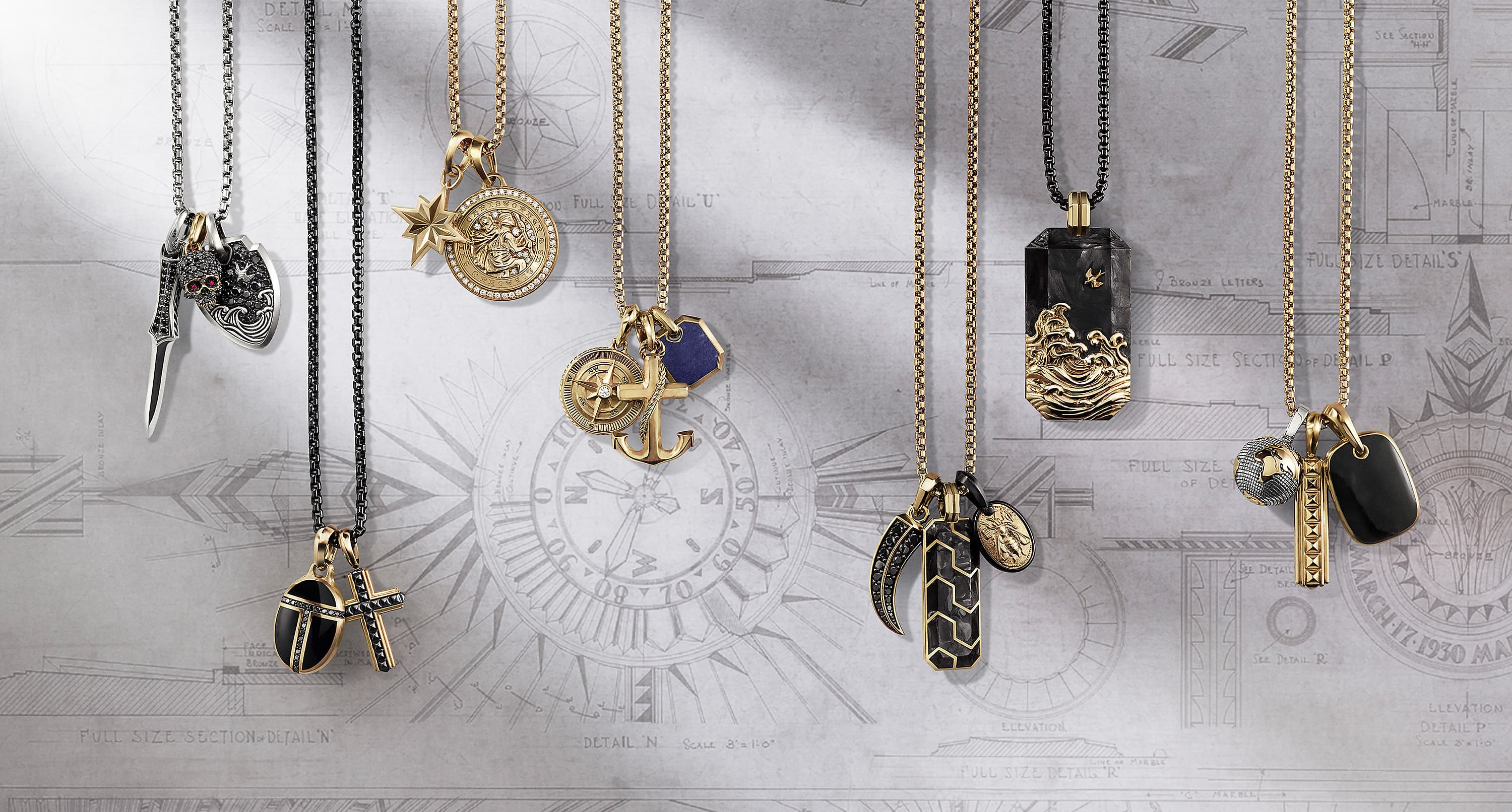 A color photo shows seven David Yurman men's box chains strung with various amulets—all hanging in front of a white-and-grey backdrop with sketches of clocks, architectural elements and soft shadows. The amulets are designed in various shapes like dog tags, a black diamond skull with rubies, a black diamond horn, a lapis lazuli octagon, the Earth and an anchor. The jewelry is crafted from sterling silver, 18K yellow gold, blackened stainless steel, forged carbon or black titanium with 18K yellow gold or mixed metals.