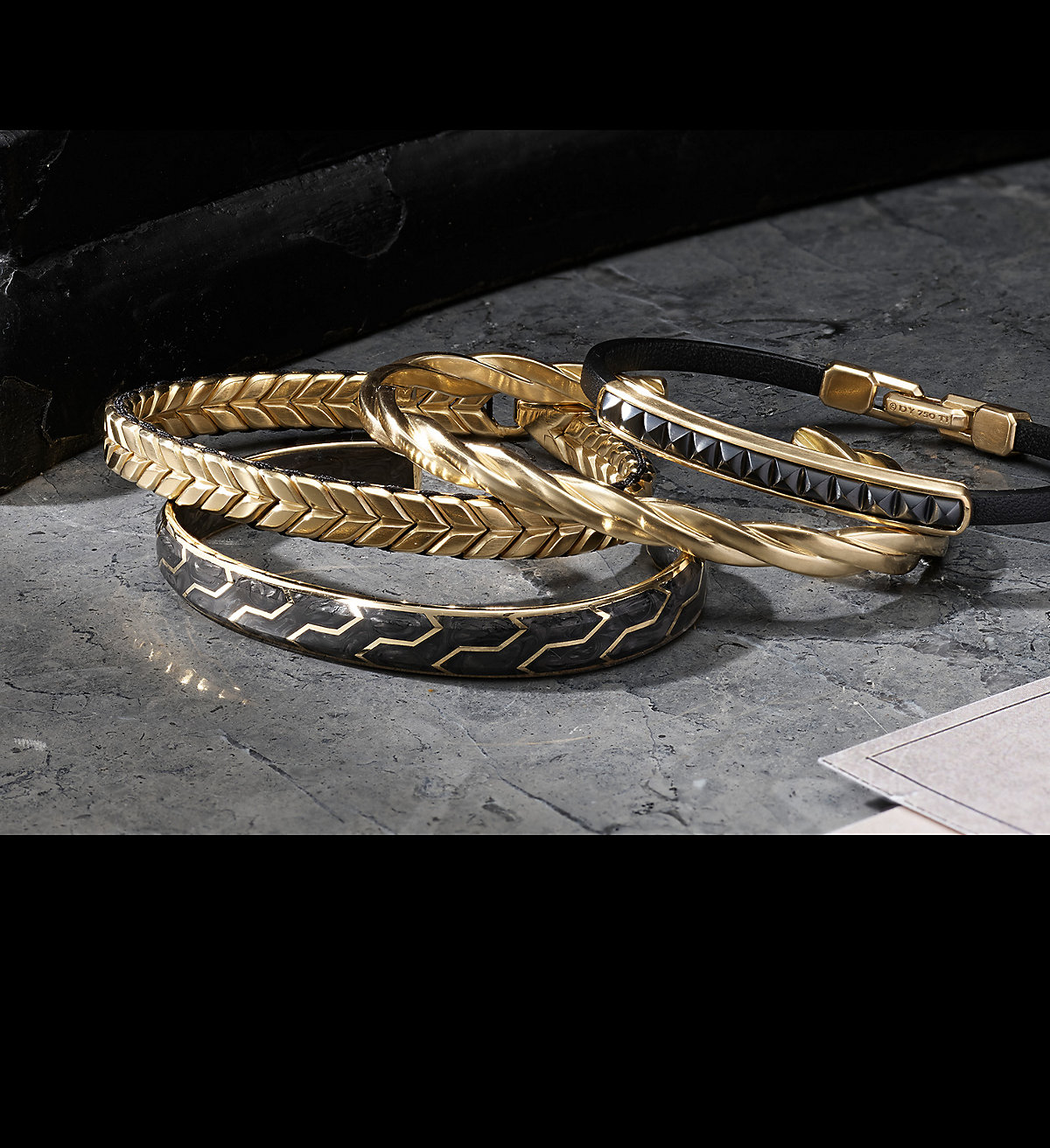 An image of four bracelets balanced atop each other on a grey marble surface with white papers and soft shadows. The jewelry is crafted from 18K yellow gold with or without black leather and black titanium in pyramid-shaped motifs or forged carbon.