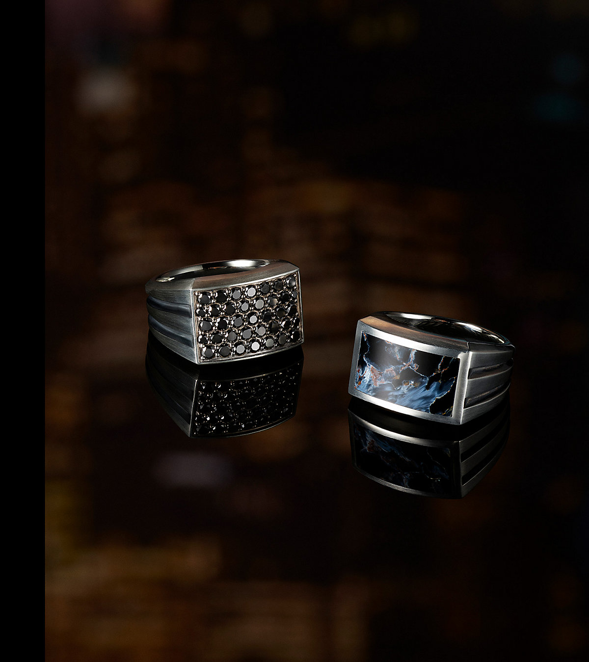 An image of two Beveled signet rings placed atop a dark reflective surface. The jewelry is crafted from sterling silver with pavé black diamonds or pietersite.