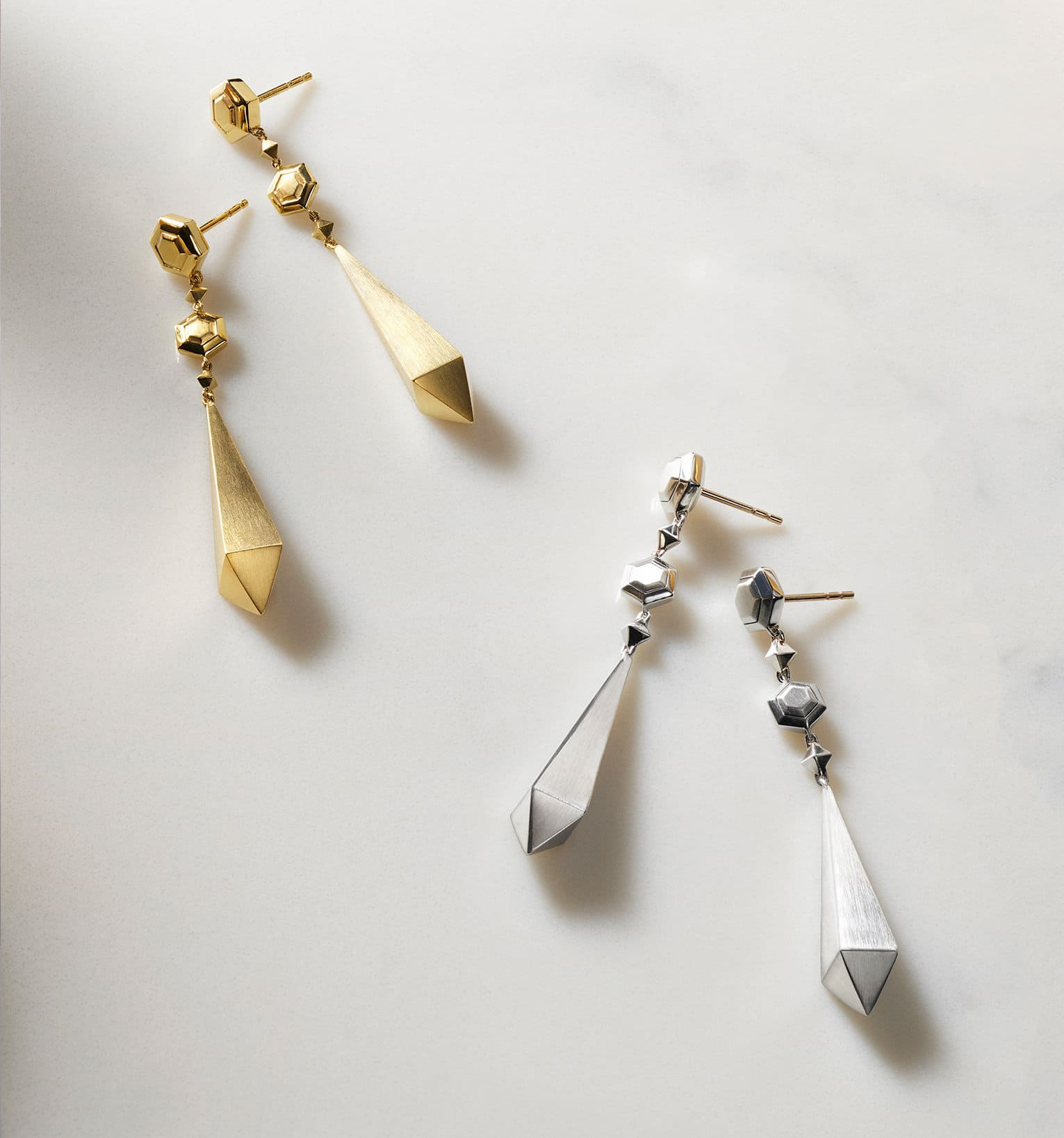 A color photo shows two pairs of David Yurman women's earrings from the Renaissance Collection scattered on a grey marble surface nearby a white-and-pink flower, a perfume bottle and a golden tray. One pair is crafted from 18K yellow gold and the other pair is crafted from sterling silver.
