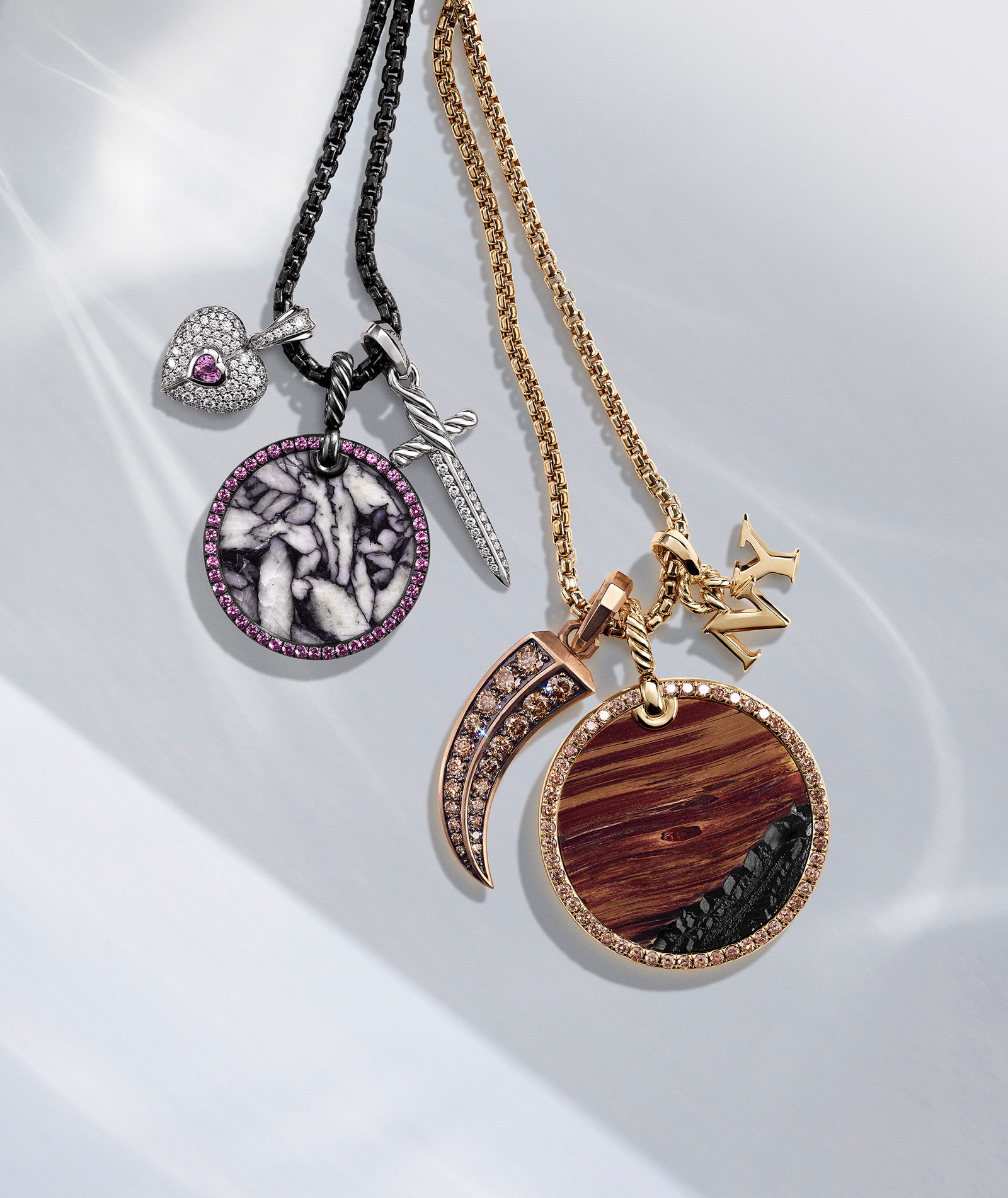 """A color photograph shows two David Yurman chain necklaces placed on a white surface, each strung with three amulets each. The amulets come in various shapes, including circles, a heart, dagger, horn and the letters """"NY."""" The jewelry is crafted from 18K yellow, rose or white gold, or darkened sterling silver with or without tiger's eye, yellow sapphires, white or cognac diamonds, pinolith, rubies or pink sapphire."""