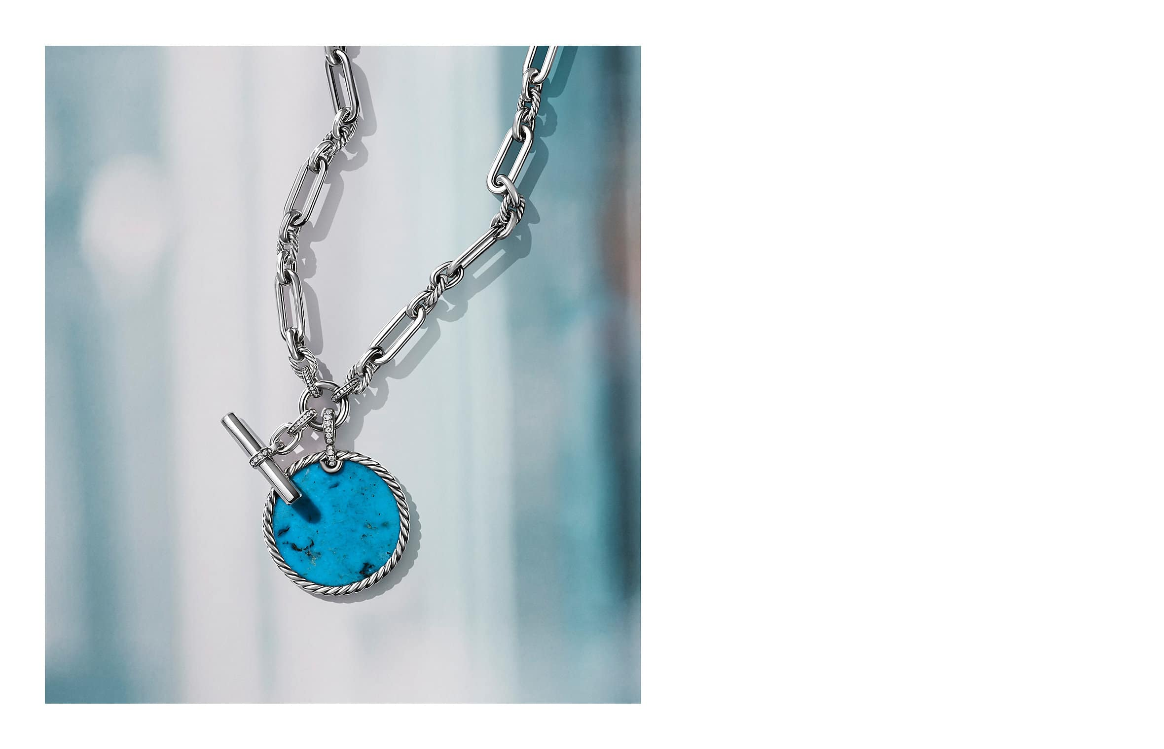 A color photo shows a DY Elements circular turquoise enhancer on a Lexington chain necklace atop a soft-focus image of a white window. The jewelry is crafted from sterling silver with or without white diamonds.