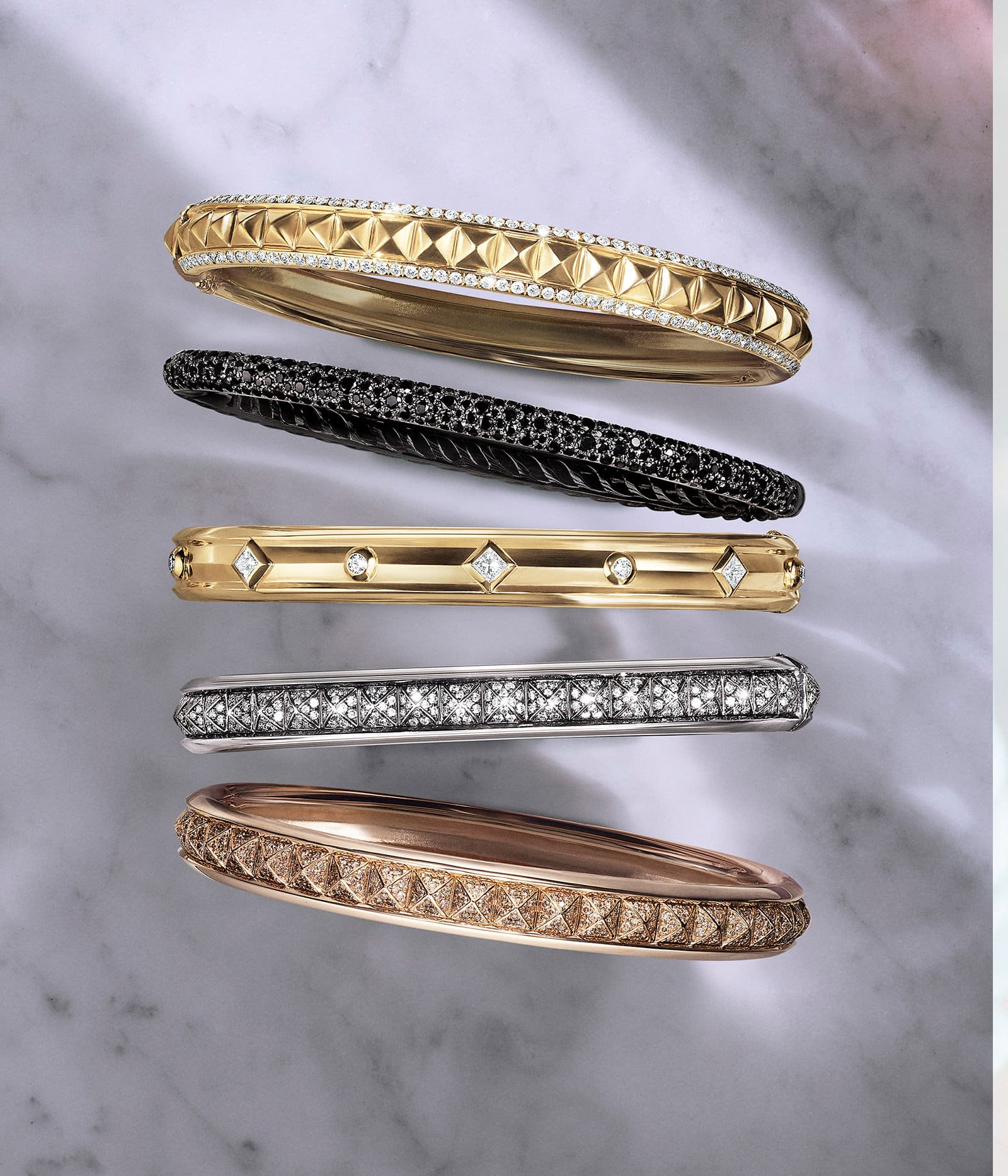 An image showing a vertical stack of five bangle bracelets from the Renaissance and Petite Pavé collections. he jewelry is crafted from 18K yellow, white or rose gold with white, cognac, grey or black diamonds.