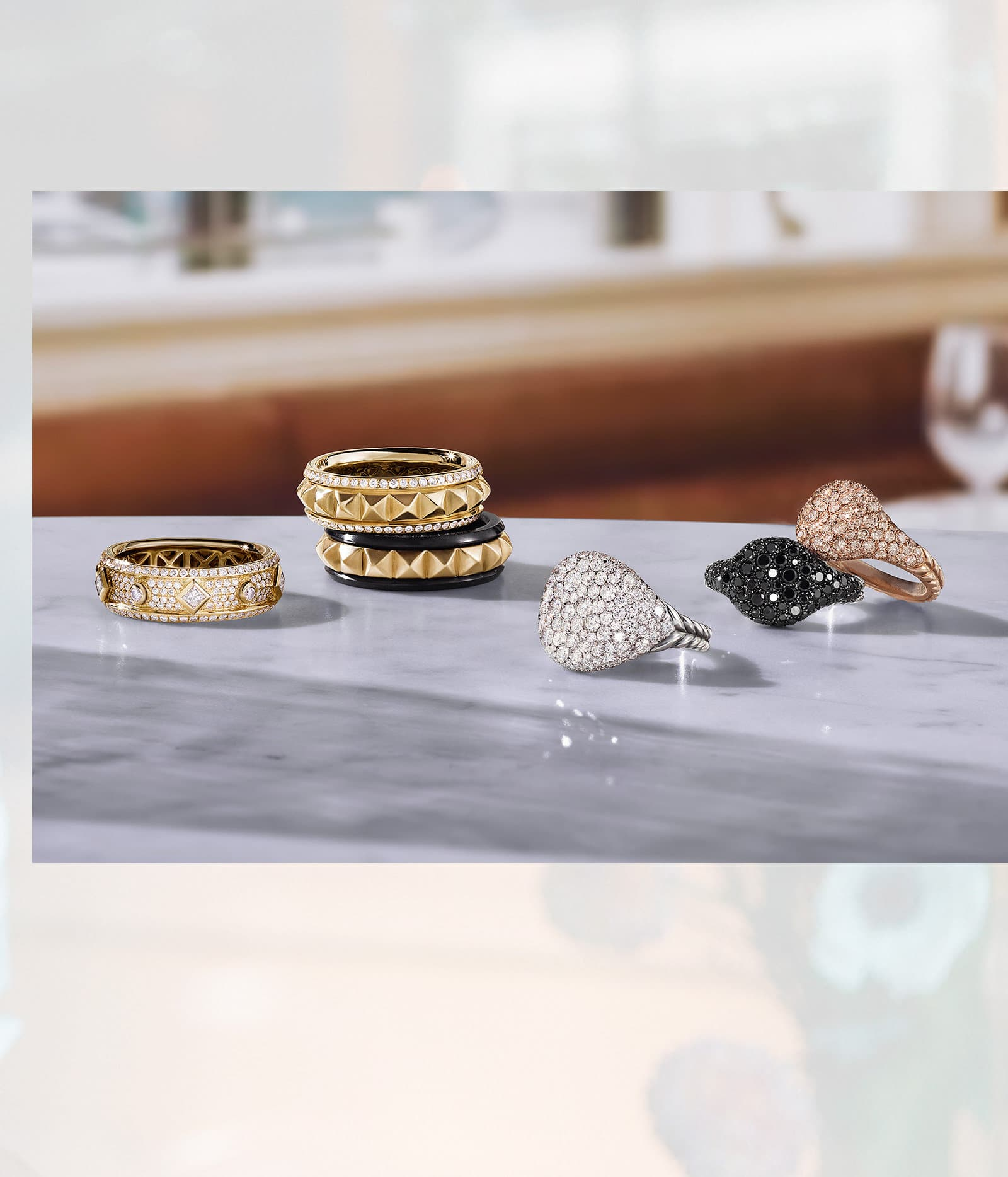 An image of three Renaissance band rings and three pinky rings scattered on a marble table. The jewelry is crafted from 18K yellow, white or rose gold with white, cognac, grey or black diamonds.