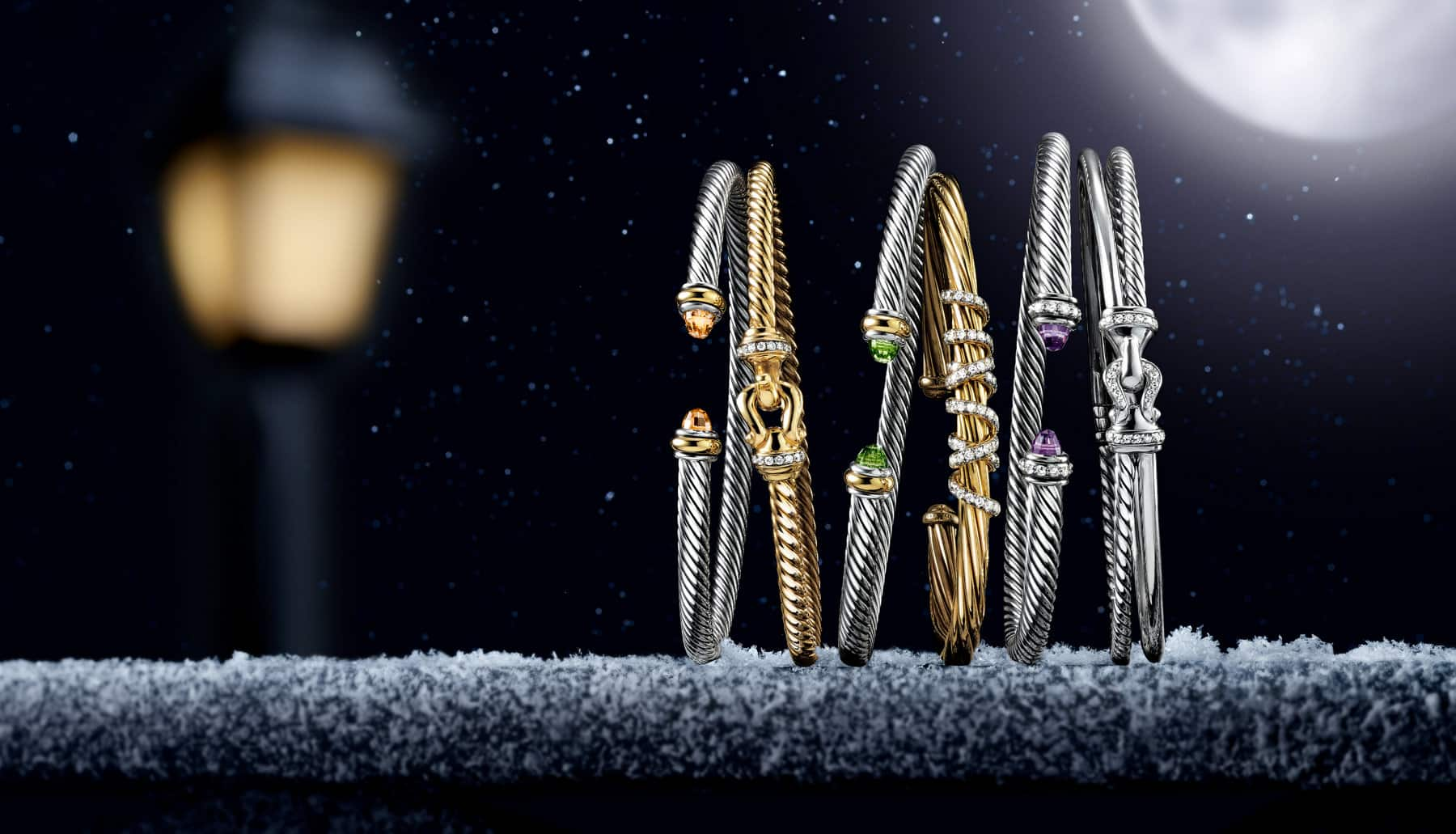 Six David Yurman bracelets from the Cable, Buckle and Helena collections are leaning against each other at night on a stone ledge lightly dusted with snowflakes. The women's jewelry is crafted from sterling silver with or without 18K yellow gold accents, white diamonds or colored gemstones, or 18K yellow gold with pavé white diamonds or amethyst. In the dark background is the golden glow of a nearby street light.