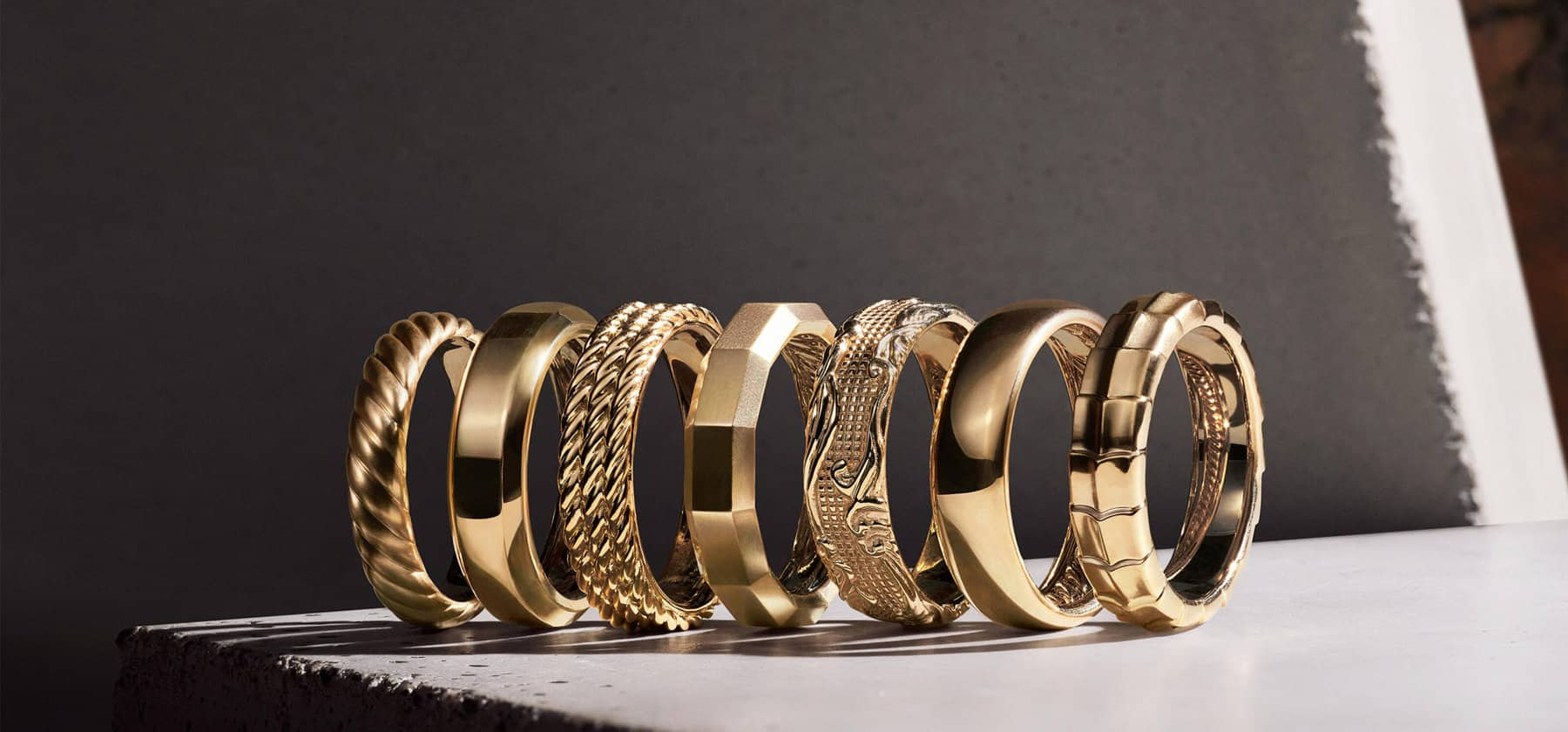 A diagonal stack of David Yurman Beveled, Forged Carbon, DY Classic, Faceted, Waves and The Cable Collection® men's bands, in a mix of precious metals, black titanium, diamonds and forged carbon, standing up on the edge of a light grey stone block and casting long shadows.