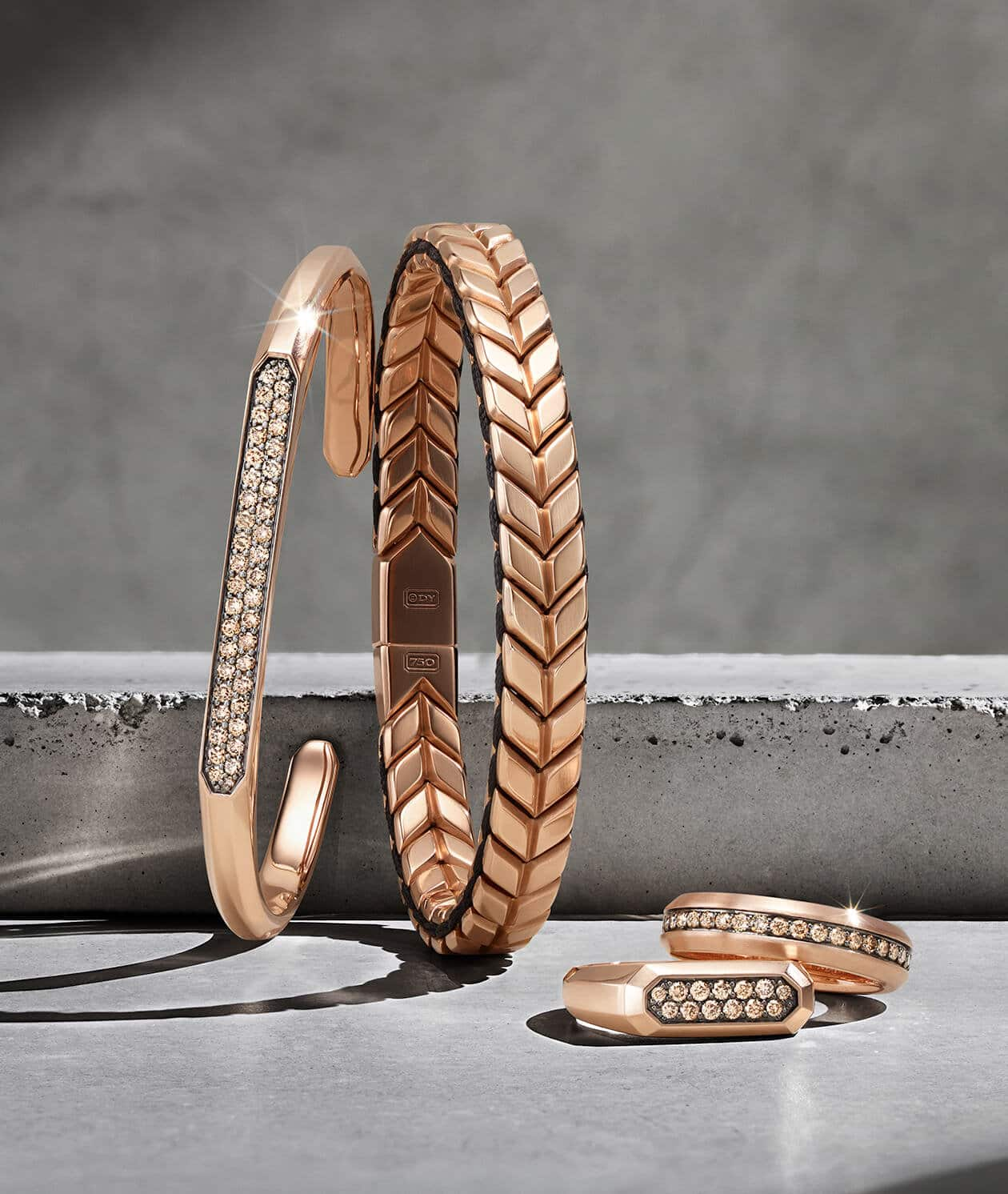 David Yurman Streamline® and Chevron bracelets and rings in 18K rose gold with or without cognac diamonds, arranged in a group on and against light grey stone blocks and casting long shadows.