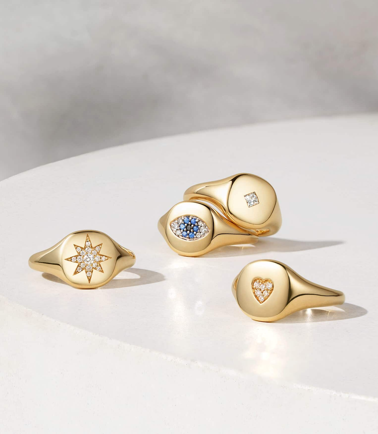 Four David Yurman pinky rings in 18K yellow gold with pavé diamonds and sapphires, all scattered on a white circular stone surface.