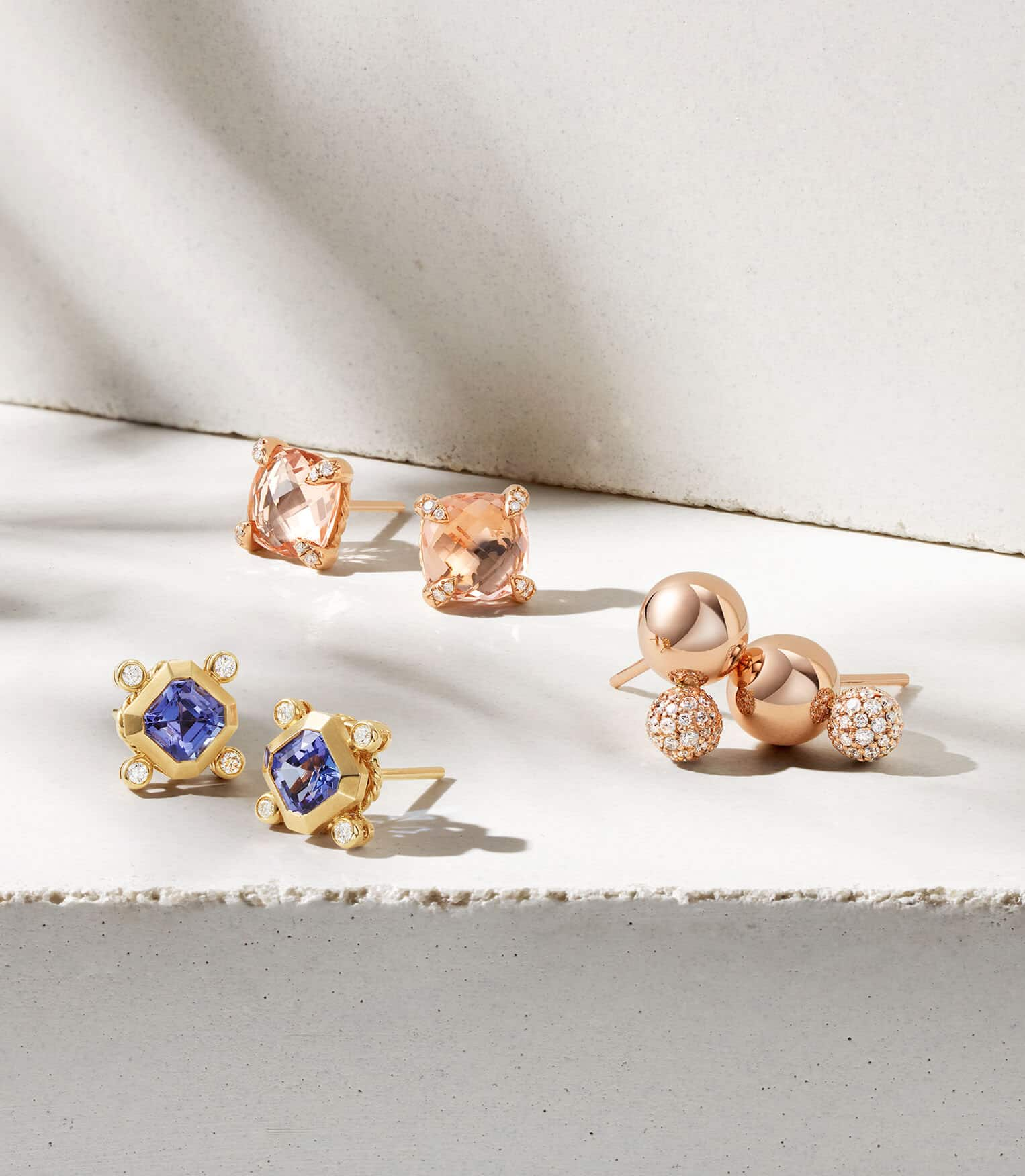A color photo of three pairs of David Yurman stud earrings in 18K yellow gold or rose gold with pavé diamonds, morganite or sapphires all scattered on top of a beige-colored stone background with shadows.
