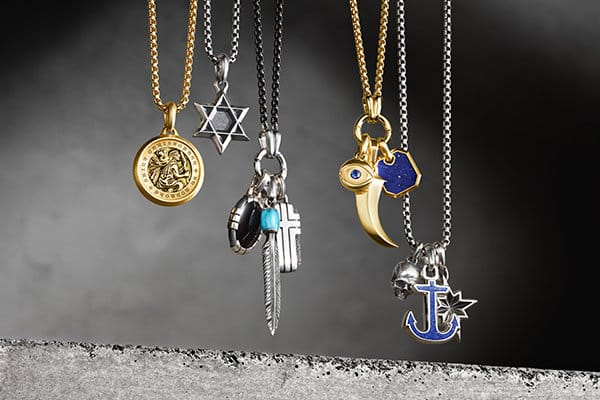 David Yurman Amulets, Southwest, Roman and Maritime® amulets, in 18K gold or sterling silver with or without black onyx, turquoise, sapphire or lapis lazuli, strung in groups on chain necklaces in precious metals or black titanium and hanging in a row above a light grey stone block.