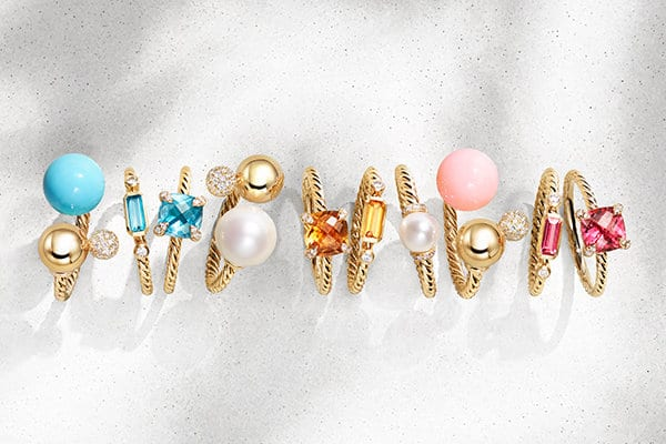 A chromatic horizontal stack of David Yurman Solari, Novella and Châtelaine® rings in 18K yellow gold with white diamonds and a variety of colored gemstones, standing on top of and casting long shadows on a white textured stone.