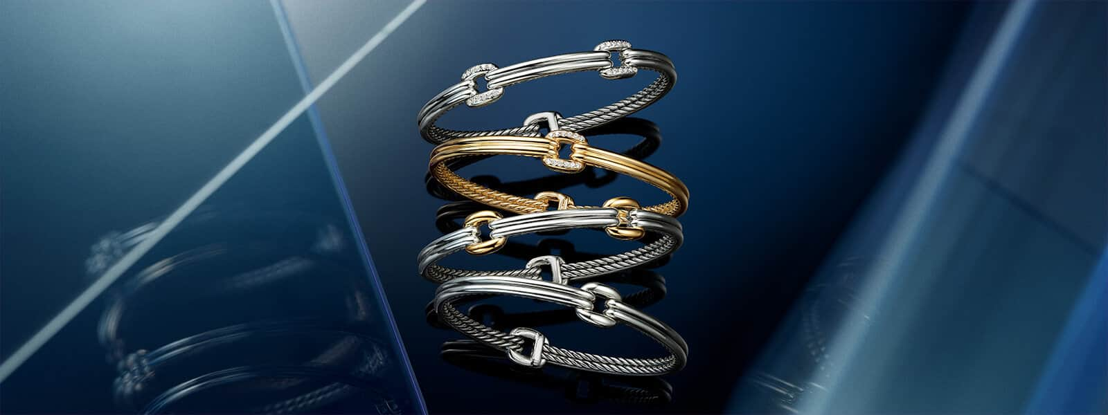 A color photograph shows four David Yurman bracelets from The Thoroughbred Collection arranged in a vertical stack atop a reflective surface with angular, multi-colored reflections of light and jewelry. From top, the bracelets are crafted from sterling silver with pavé white diamonds; 18K yellow gold with pavé white diamonds; sterling silver with 18K yellow gold accents; and sterling silver.